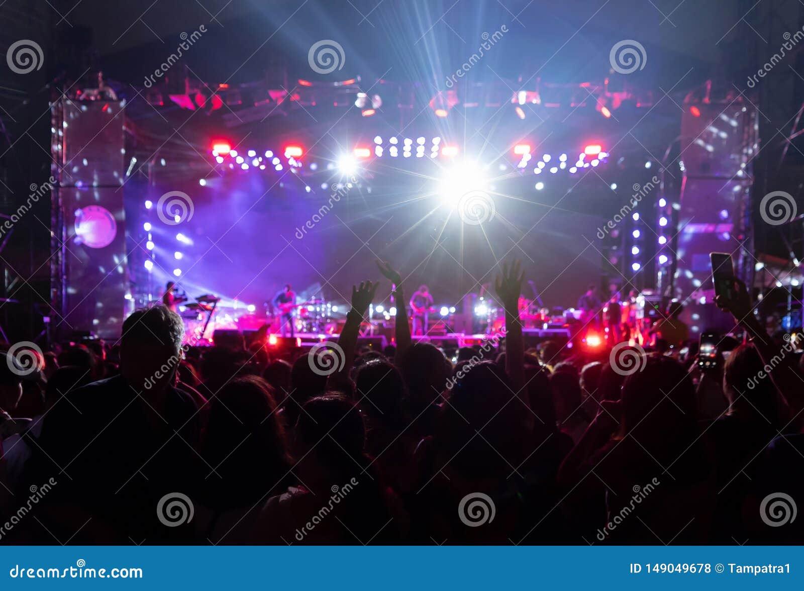 Siluetas de la muchedumbre, grupo de personas, animando en concierto de la m?sica en directo delante de luces coloridas de la eta