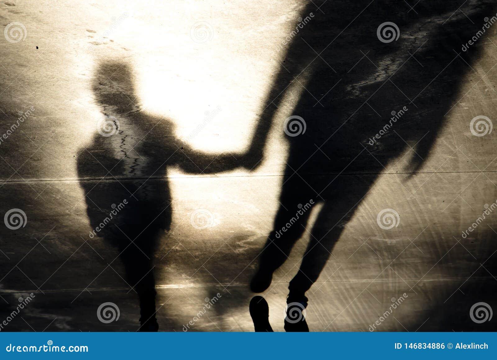 Siluetas de la sombra del padre y del hijo que caminan de común acuerdo