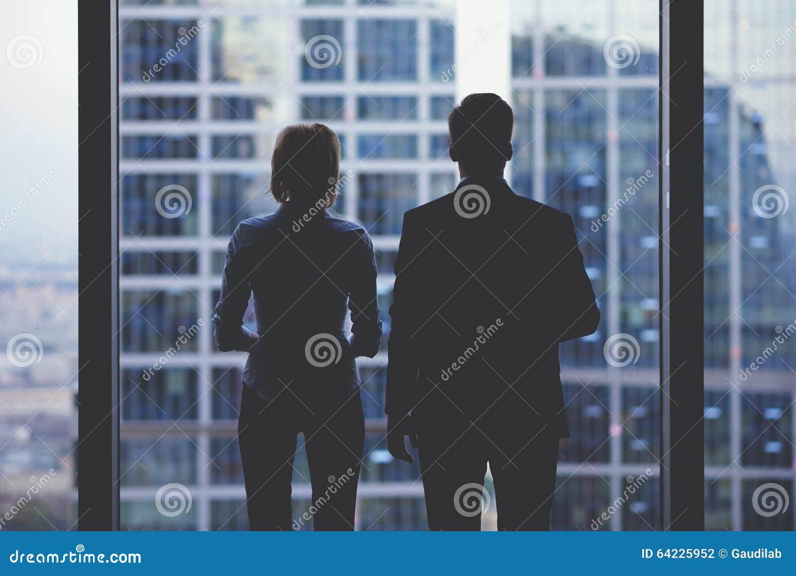 Siluetas de la vista posterior de dos socios comerciales que miran cuidadosamente fuera de una ventana de la oficina en la situac