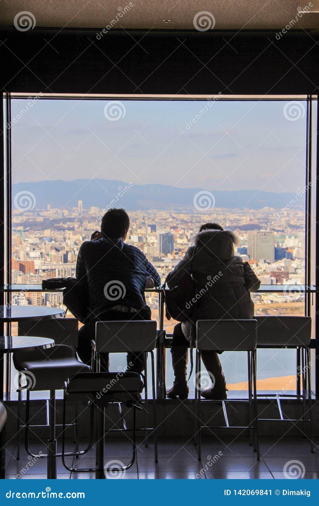Siluetas de los hombres que se sientan por la ventana grande en fondo de la vista panorámica de Osaka
