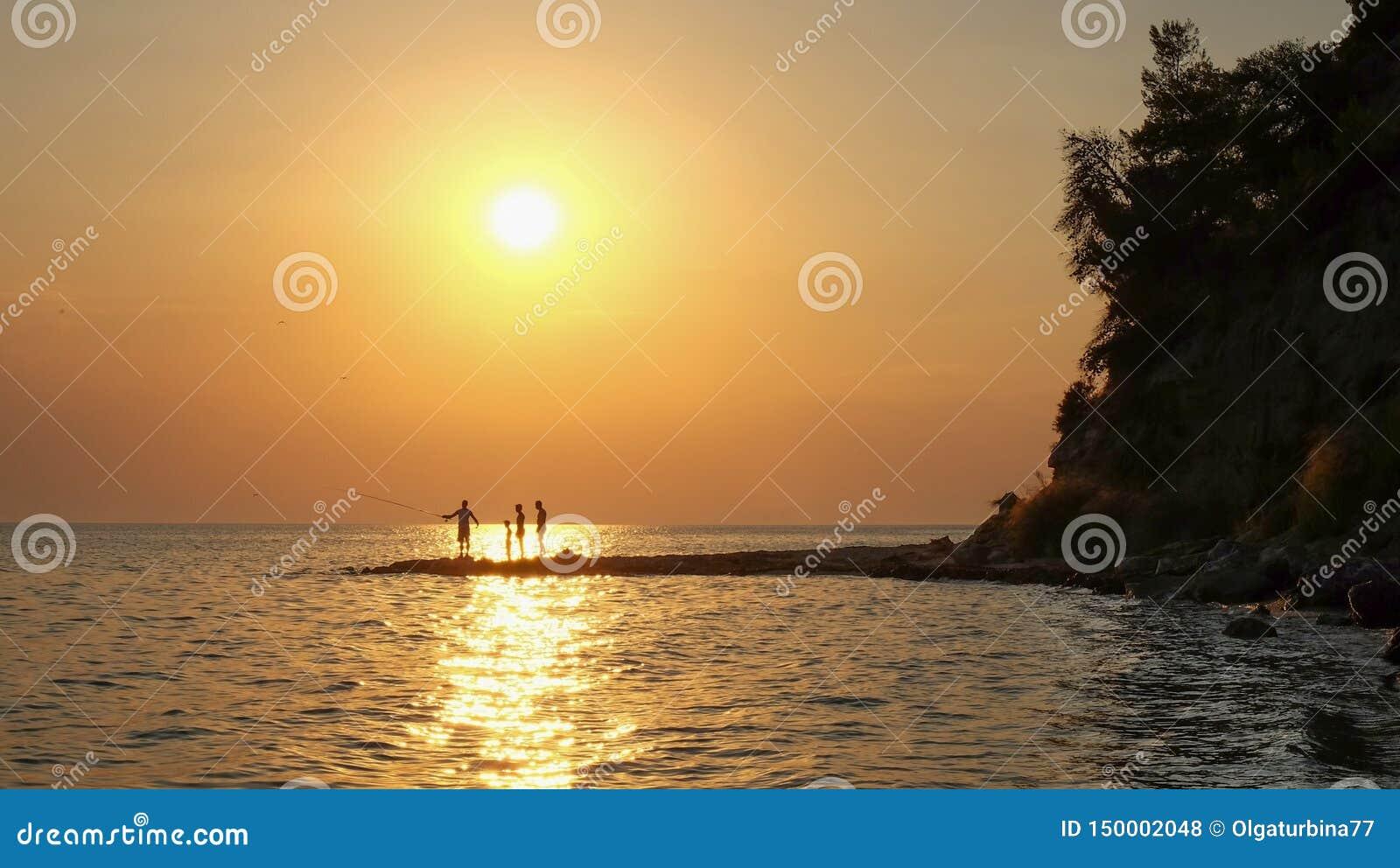 Siluetas de los pescadores que pescan en la playa