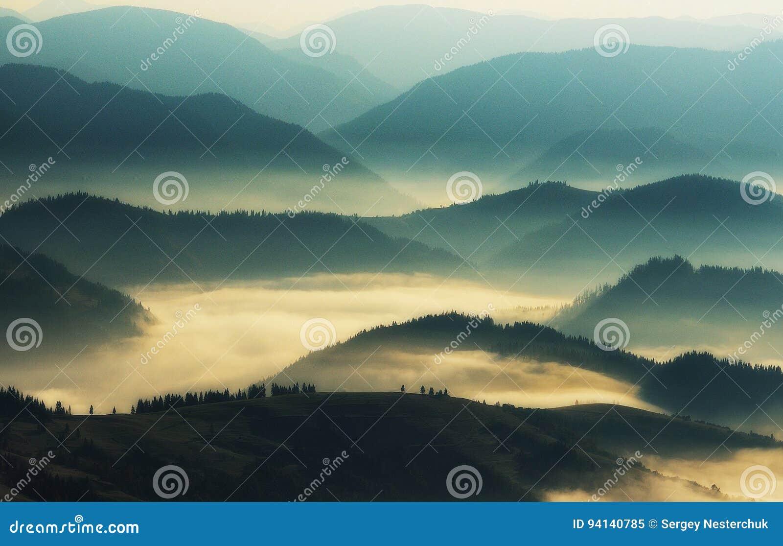 Siluetas de montañas Una mañana brumosa del otoño Amanecer en los Cárpatos