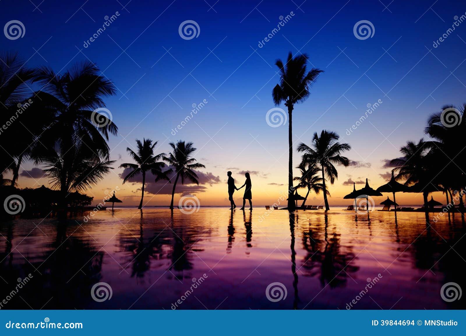Siluetas de pares jovenes en la puesta del sol escénica