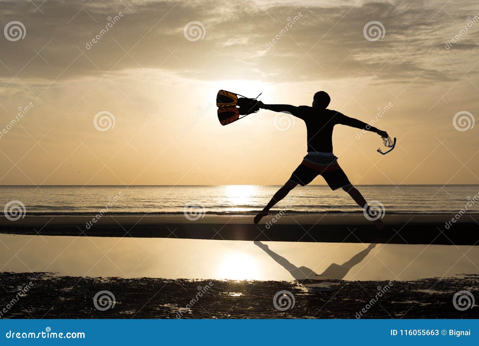Siluetee al hombre con la aleta y enmascare el salto en la playa