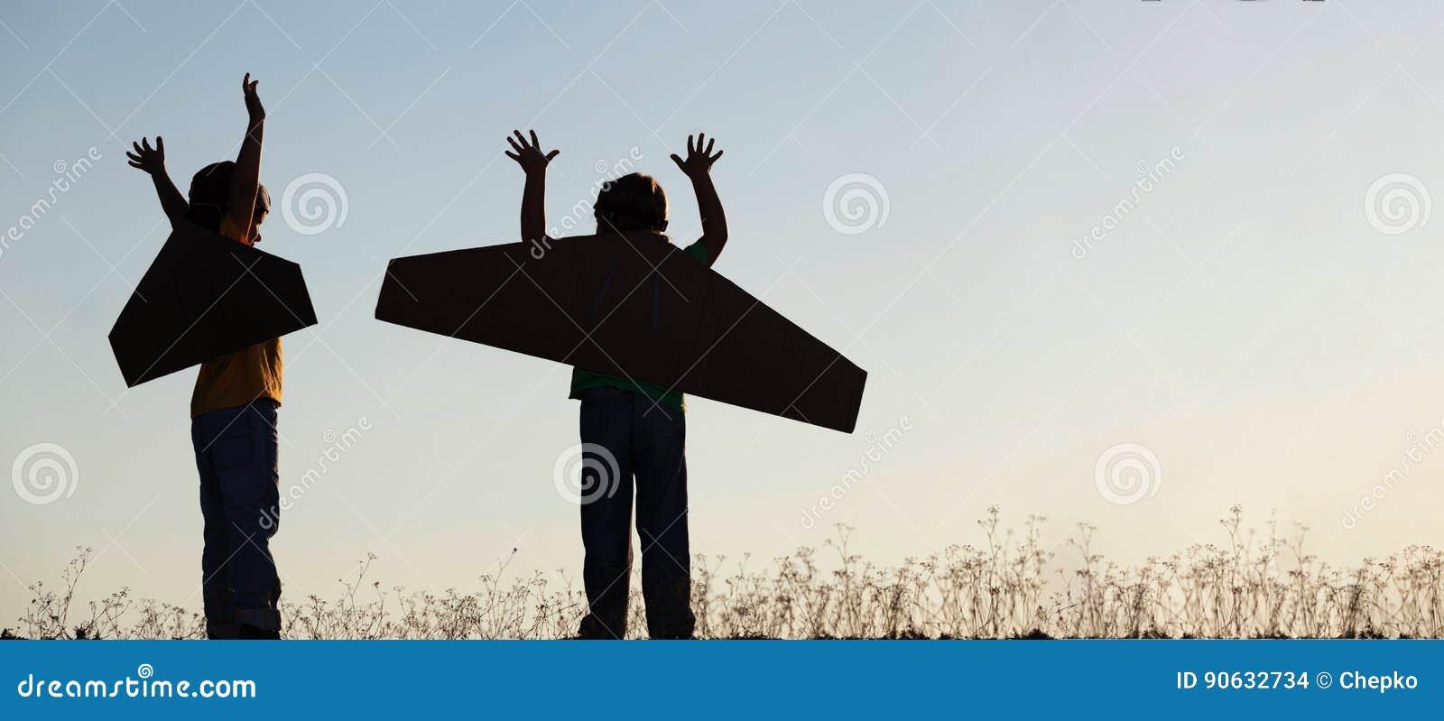 Siluetee al muchacho con las cajas de cartón de alas contra el sueño o del cielo