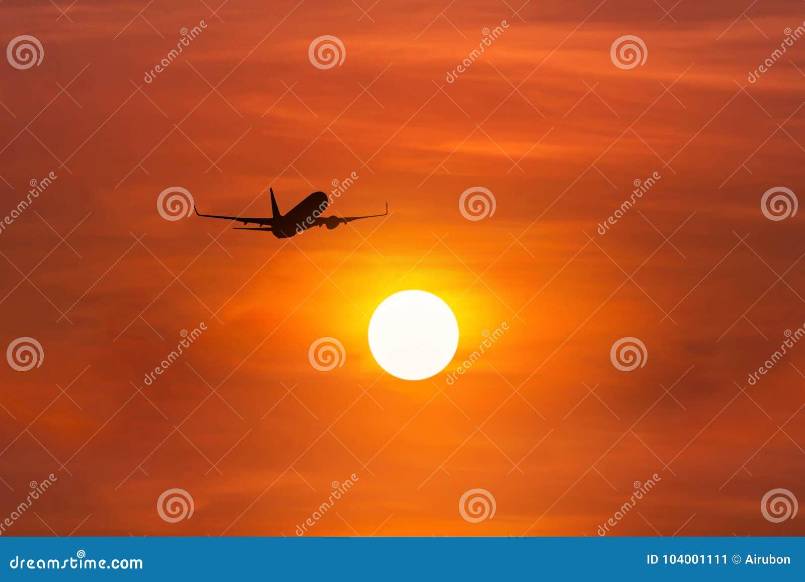 Siluetee el aeroplano del pasajero que se va volando adentro a la altitud altísima sobre el sol durante tiempo de la puesta del s