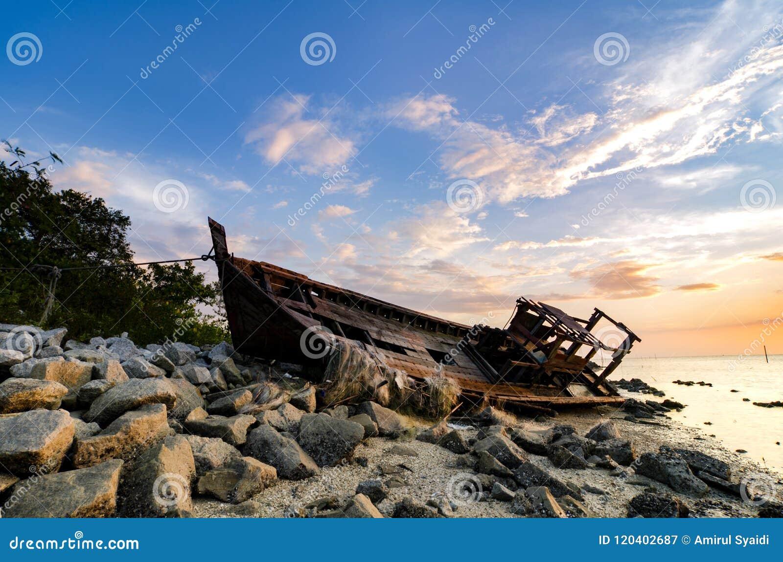 Siluetee la imagen del abandono naufragada en línea de la playa rocosa nube oscura y suavemente en el agua