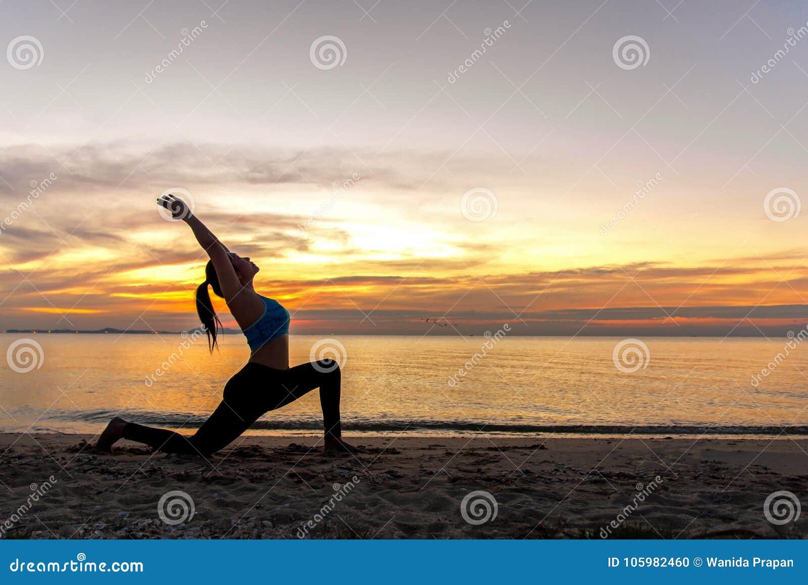 Siluetee a la mujer joven que el ejercicio de la forma de vida vital medita y bola practicante de la yoga en la playa