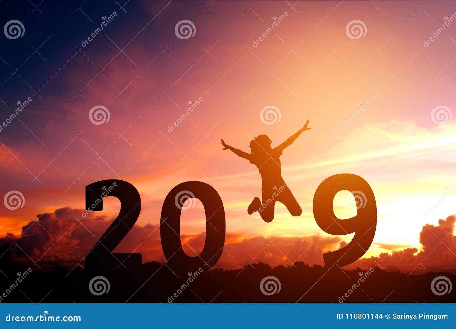 Siluetee a la mujer joven que salta a 2018 Años Nuevos
