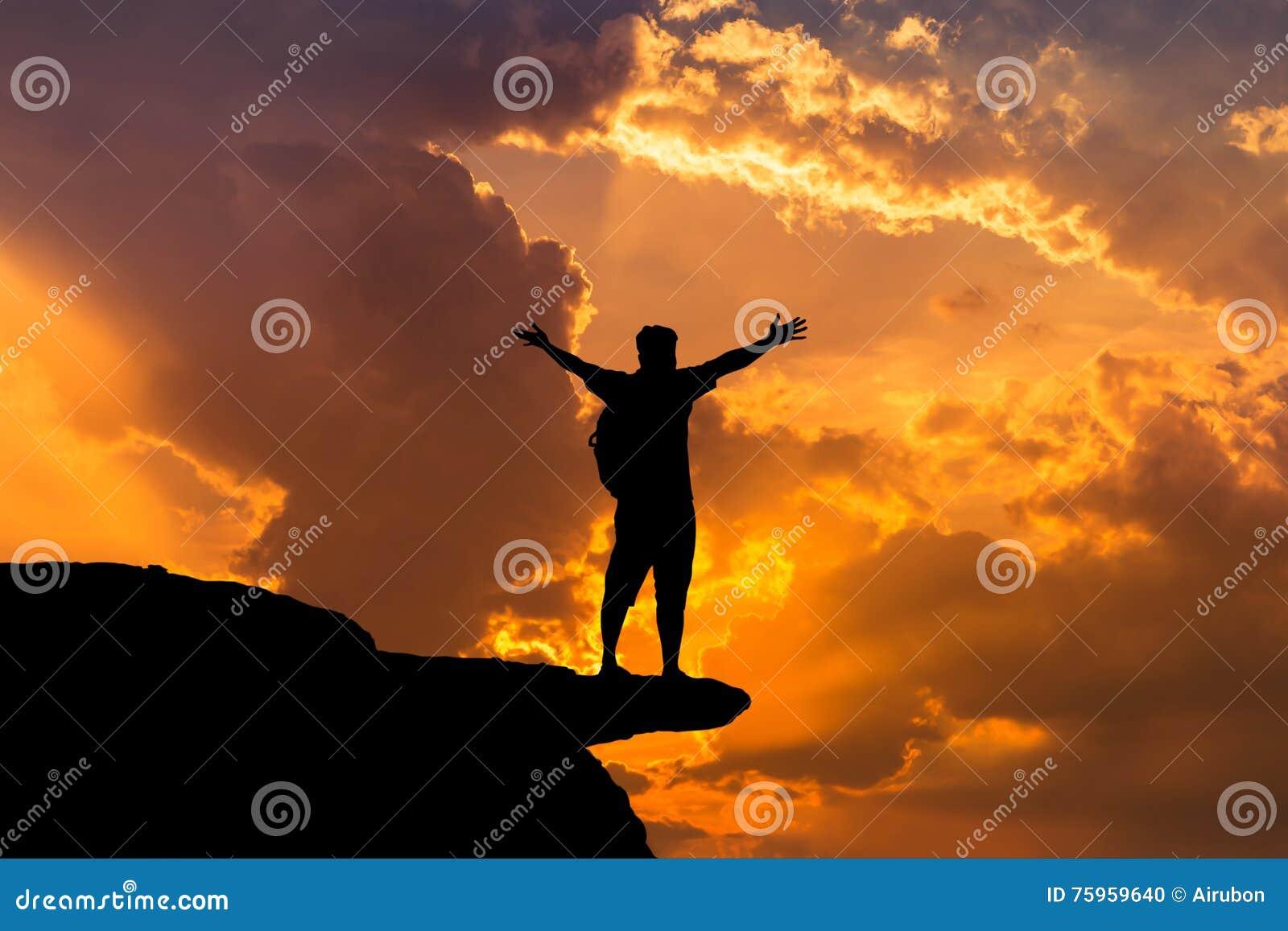 Siluetee la situación del backpacker del hombre aumentada encima de los logros de los brazos acertados y celebre el éxito encima