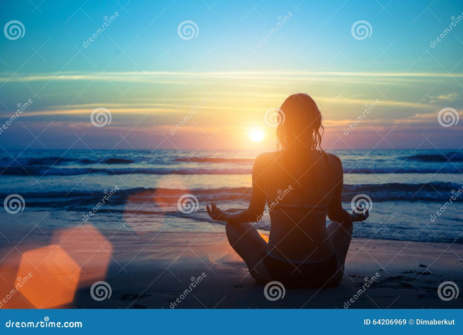 Siluetee la yoga practicante de la mujer en la playa en la puesta del sol