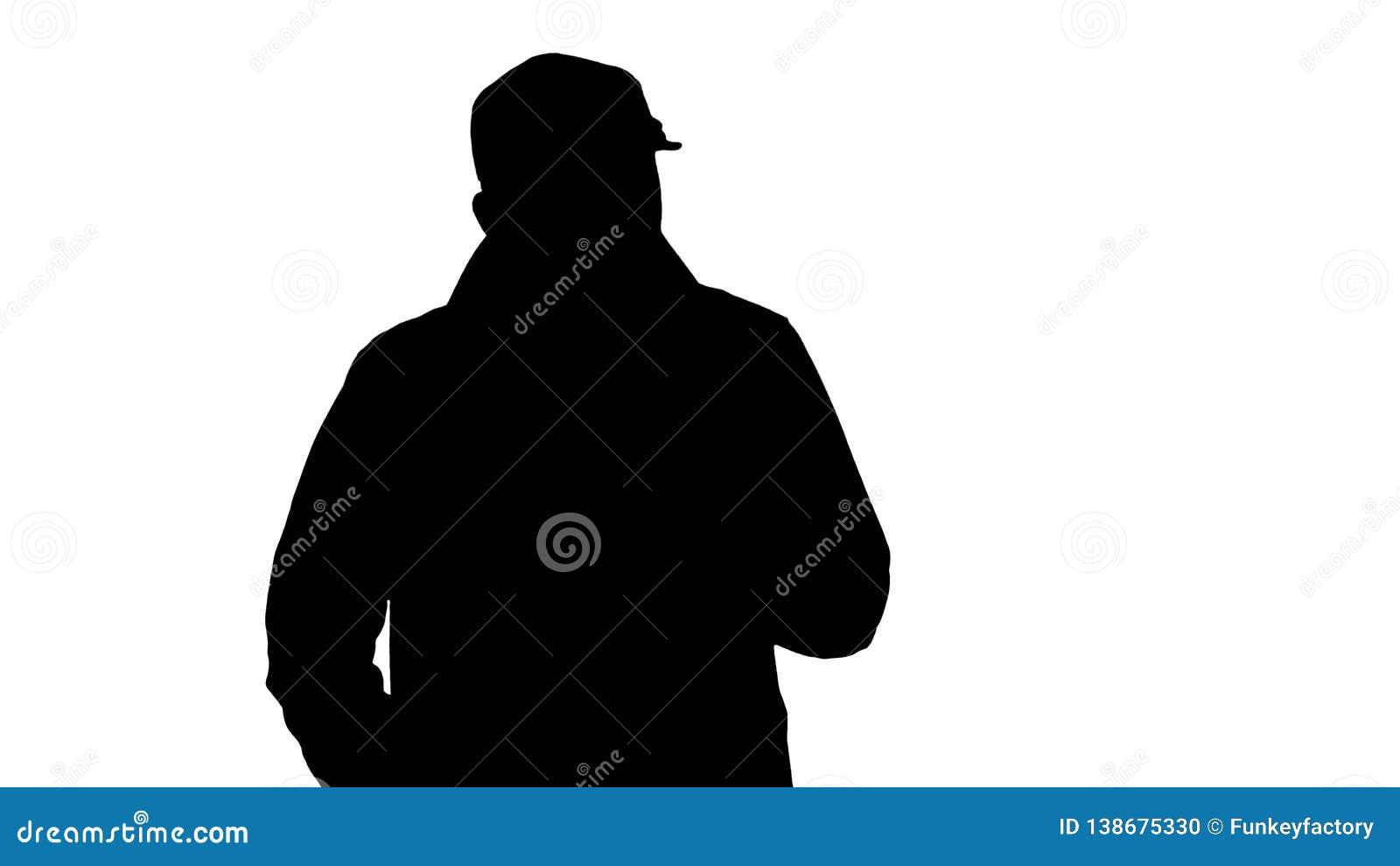 Siluetee a un varón barbudo positivo vestido en una trenca que camina y que habla