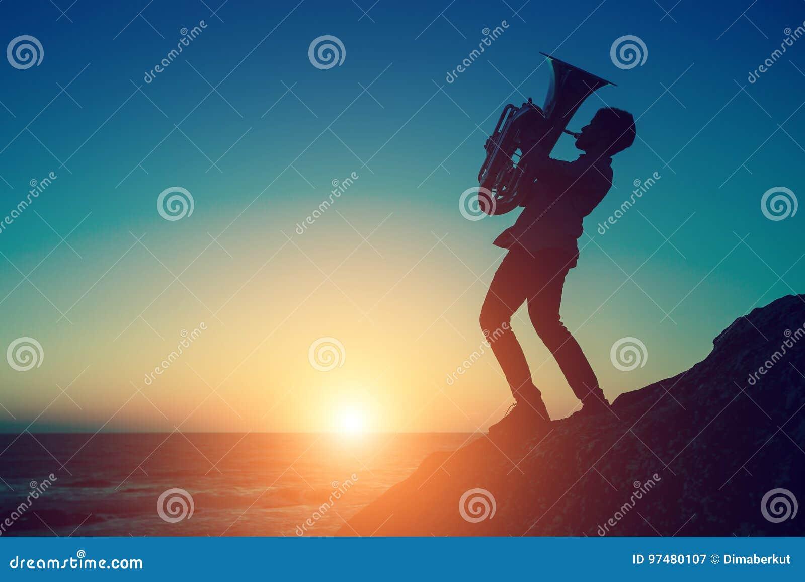 Siluetta al tramonto di uno strumento musicale della tuba del gioco del musicista sulla riva di mare all aperto hobby