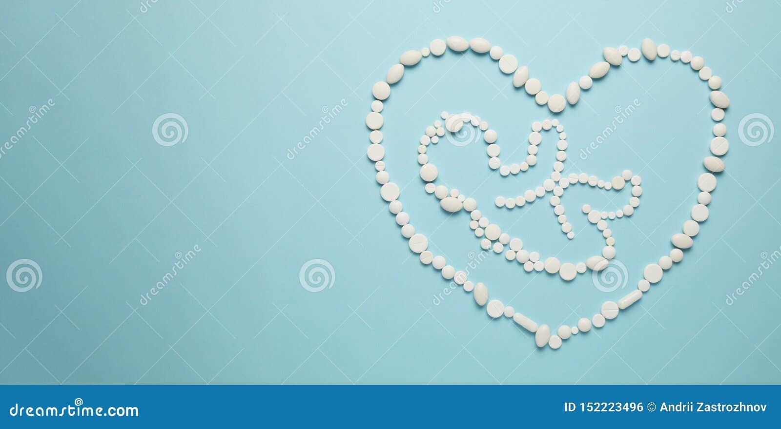 Siluetta del bambino dell embrione della gente nel cuore delle compresse bianche su fondo blu Trattamento dei neonati, assistenza