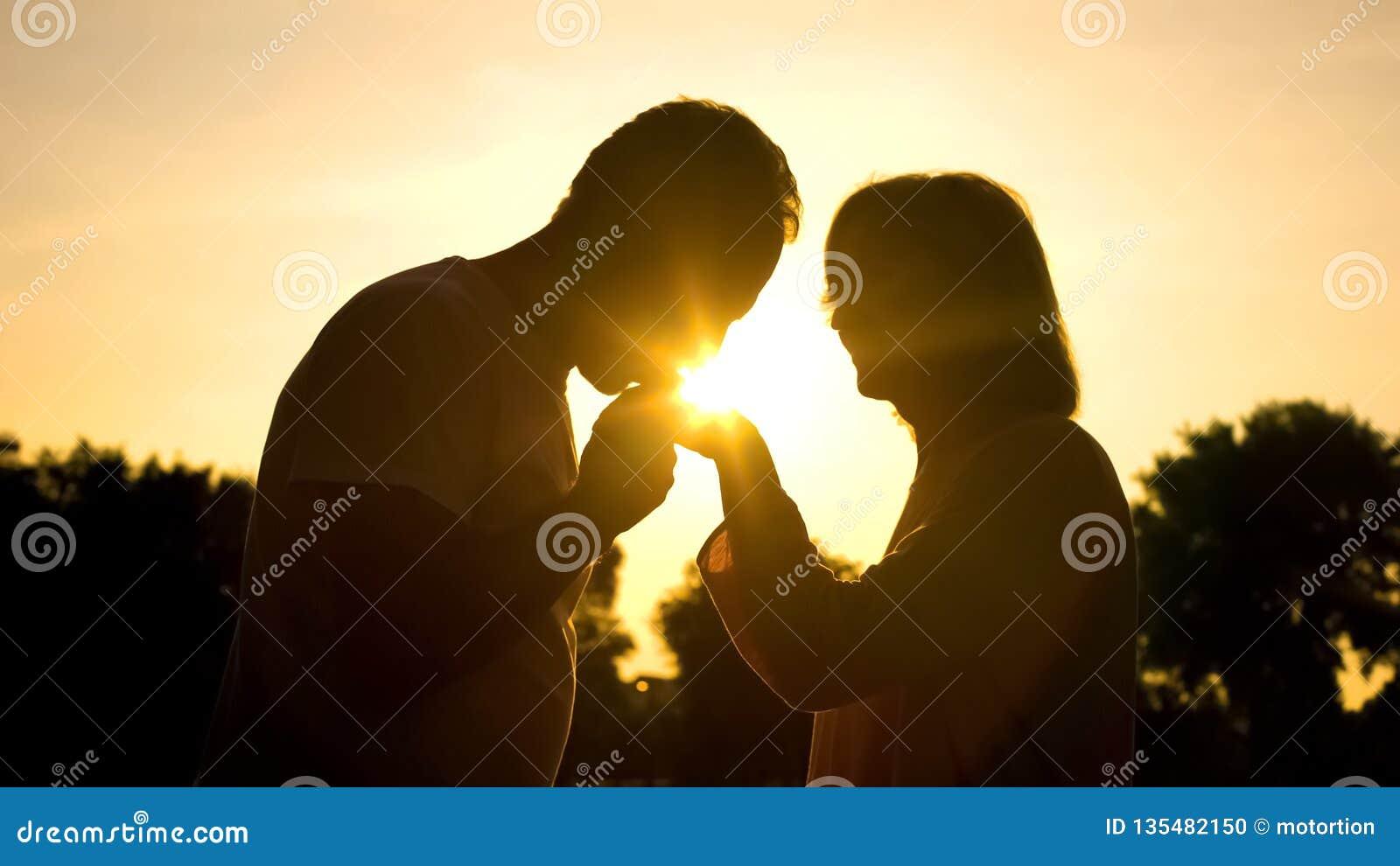 Siluetta del signore che bacia la mano della moglie, coppia senior nell amore, romanzesco