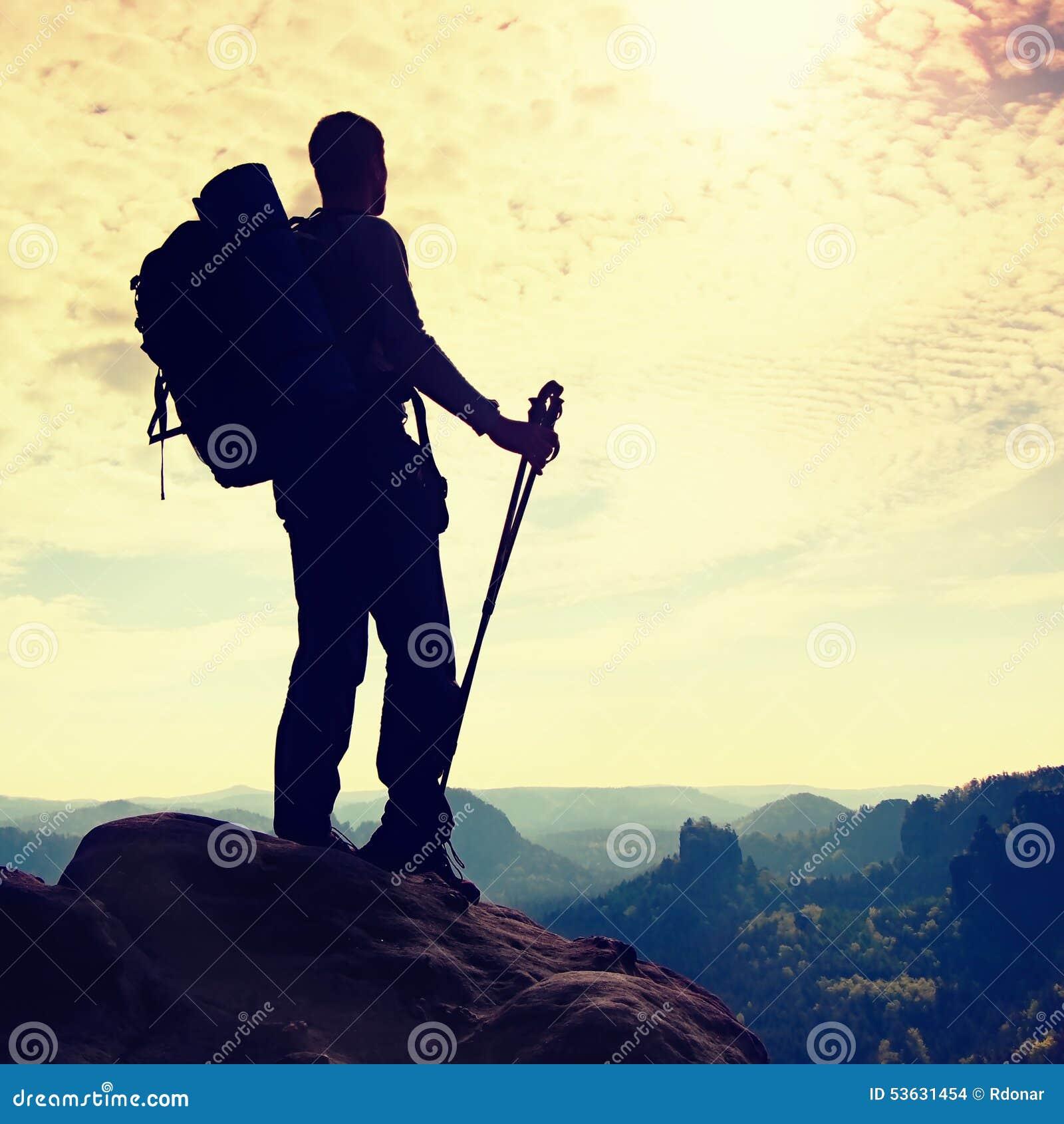 Siluetta del turista con i pali a disposizione Viandante con il grande supporto dello zaino sul punto di vista roccioso sopra la