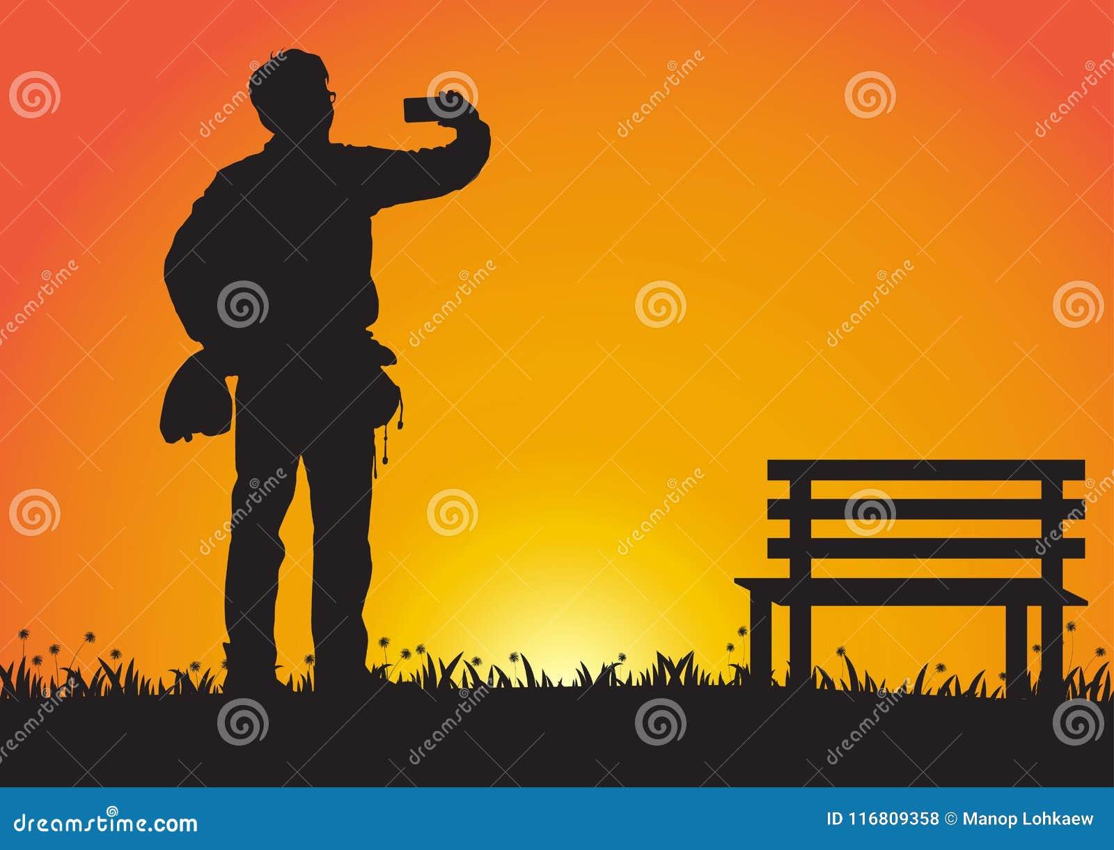Siluetta dell uomo che per mezzo del telefono cellulare sul fondo dorato di tramonto