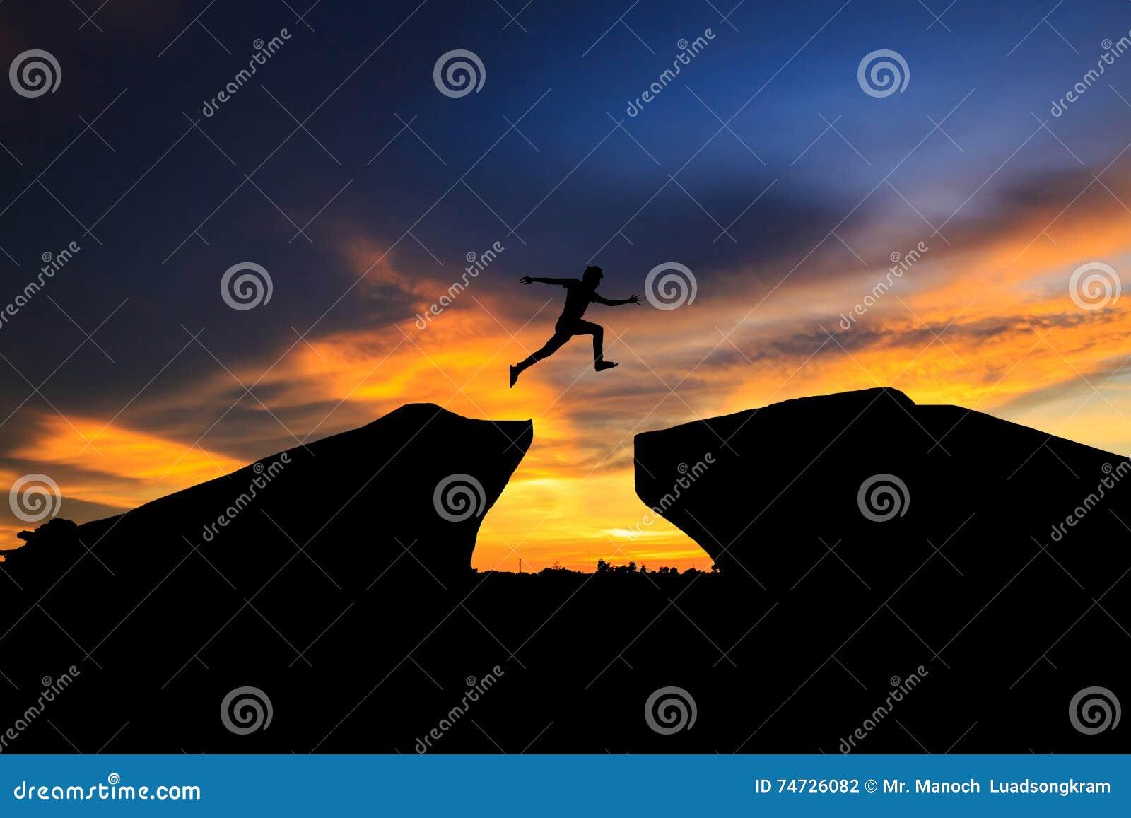 Siluetta dell uomo che salta sopra la scogliera sul fondo di tramonto