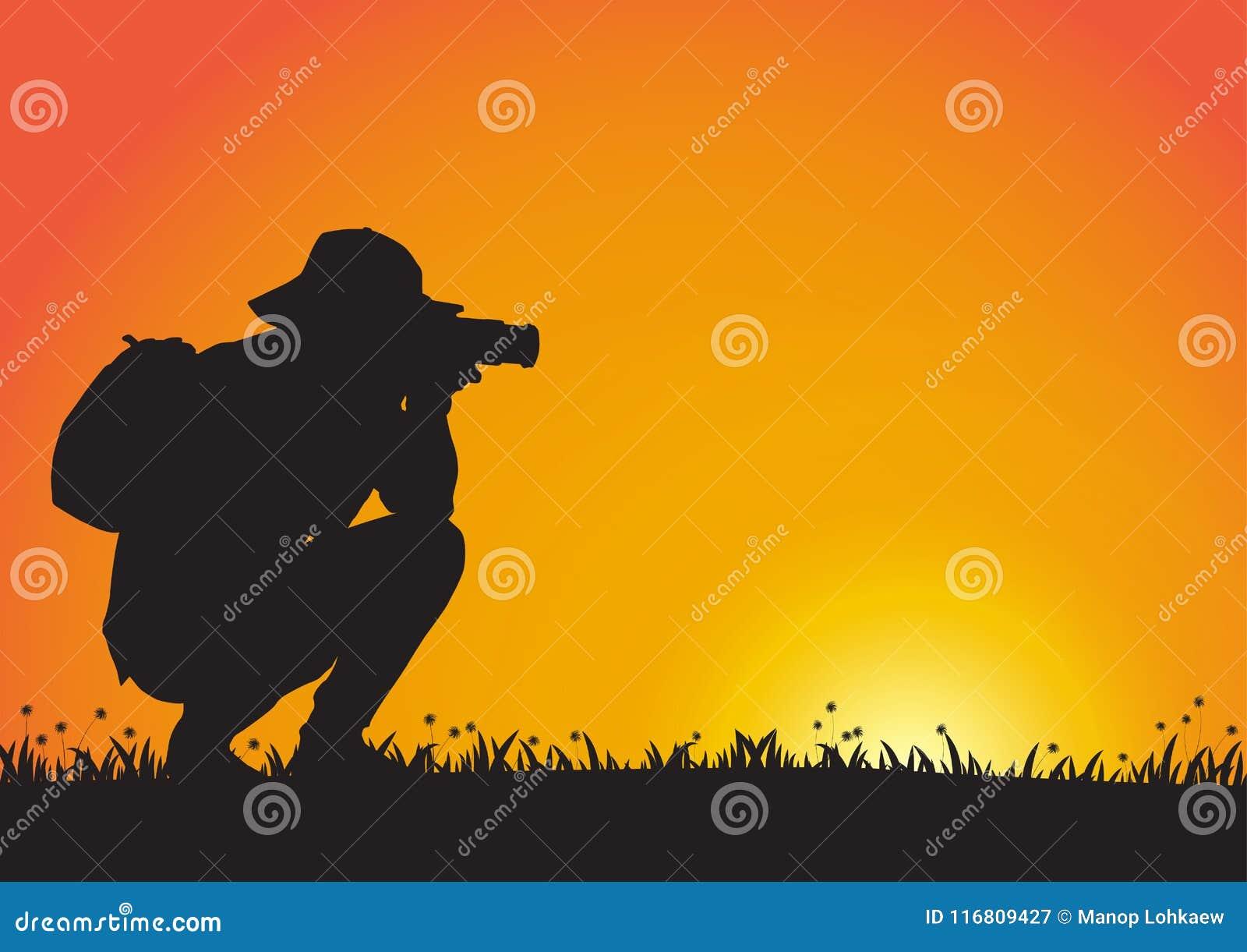Siluetta dell uomo che usando macchina fotografica sul fondo dorato di tramonto