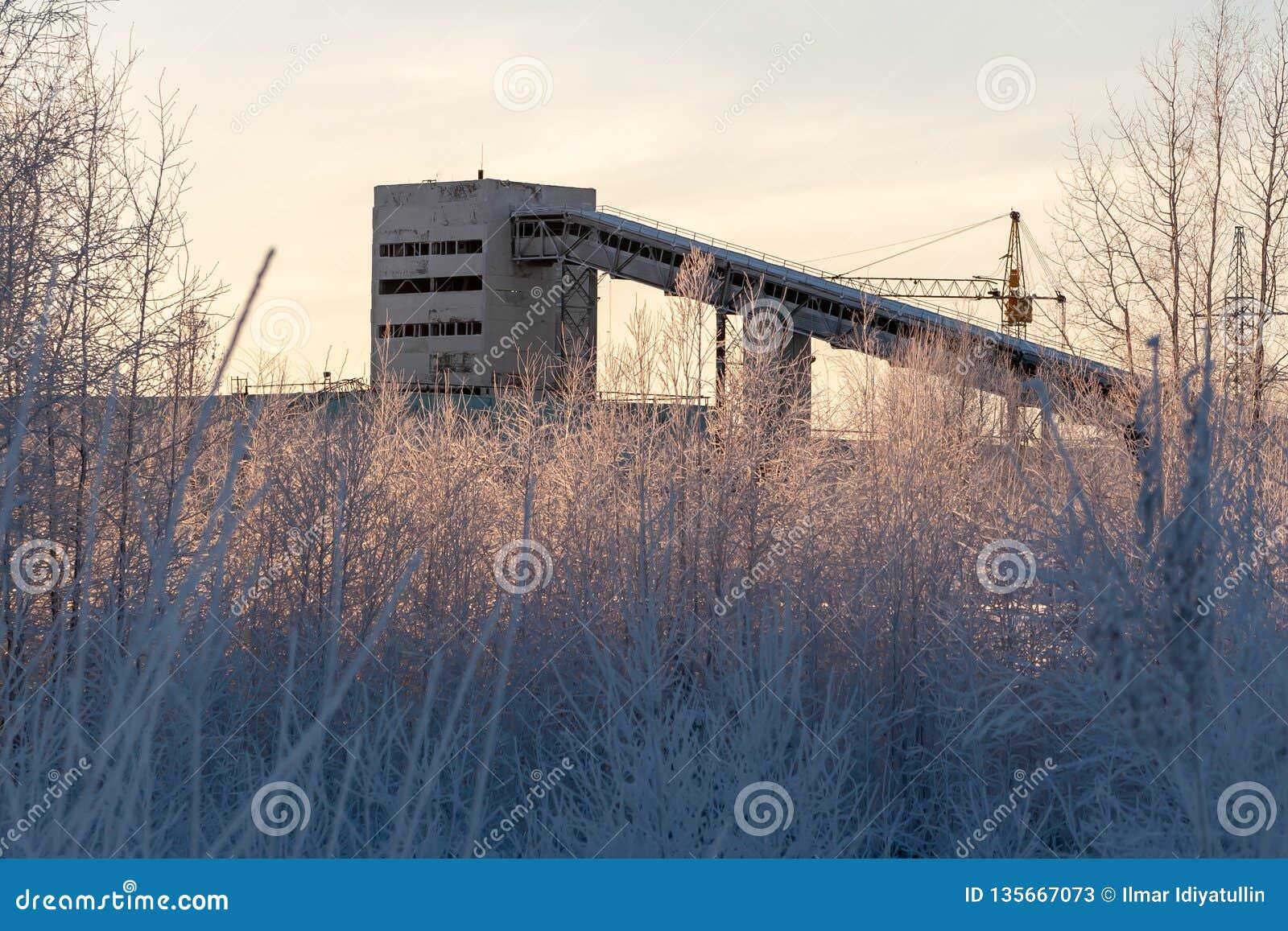 Siluetta della fabbrica che costruisce i conglomerati per la produzione di cemento nell inverno
