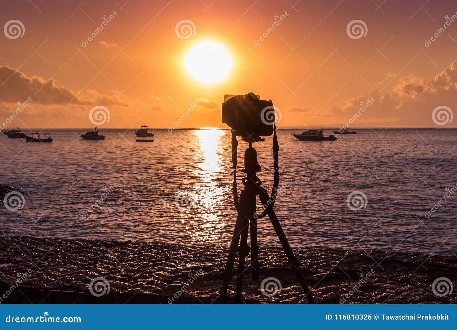 Siluetta della macchina fotografica sul mare della fucilazione del treppiede con il tramonto