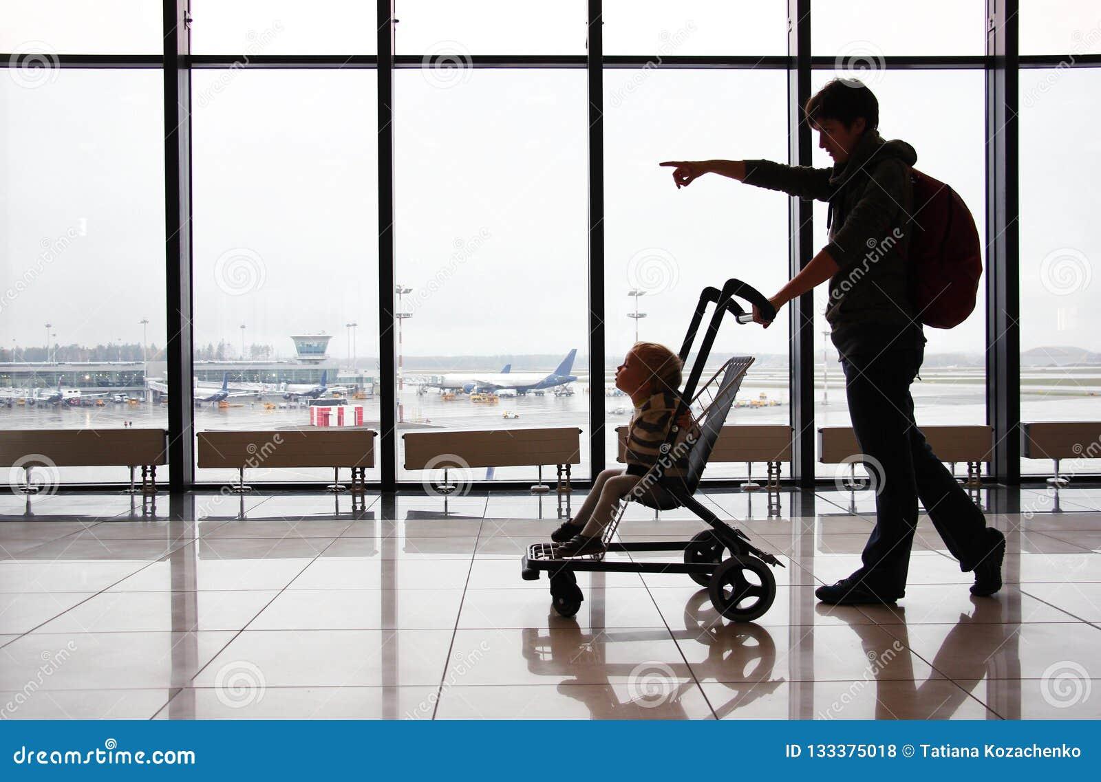 Siluetta della madre con suo figlio del bambino in passeggiatore contro la finestra all aeroporto Punti della mamma la direzione