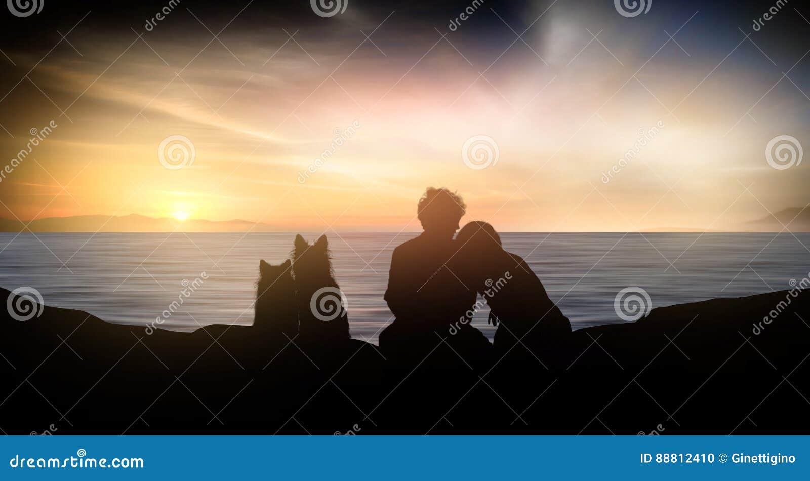 Siluetta di giovane coppia della gente e dei cani