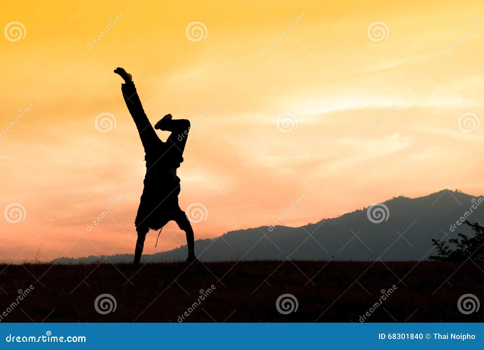 Siluetta di giovane uomo acrobatico che sta sulle mani
