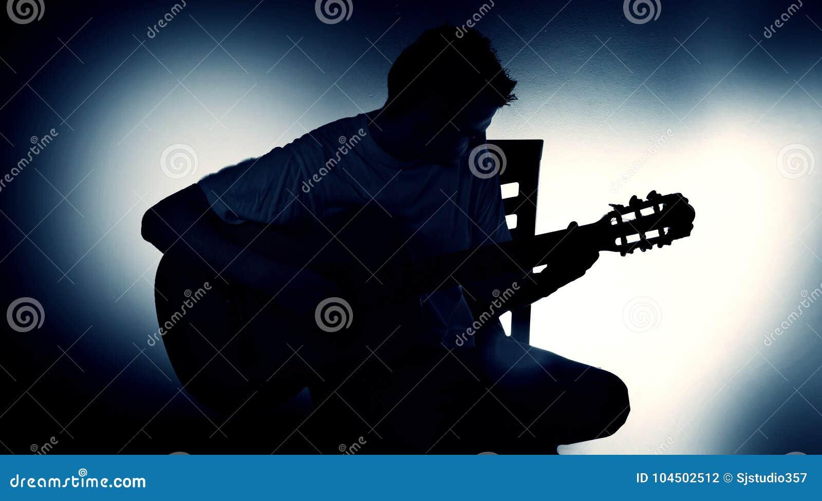 Siluetta di un chitarrista con una chitarra acustica che si siede su una sedia, fondo nero