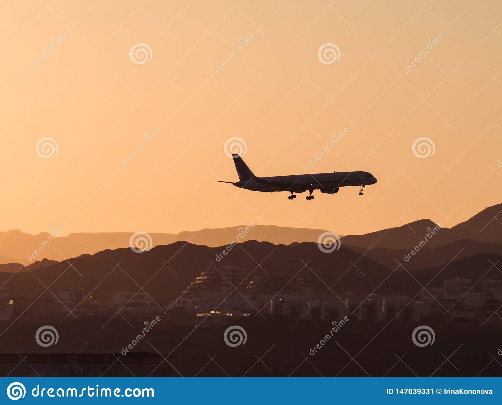 Siluetta di un minimo volante piano sopra la città e le montagne al tramonto