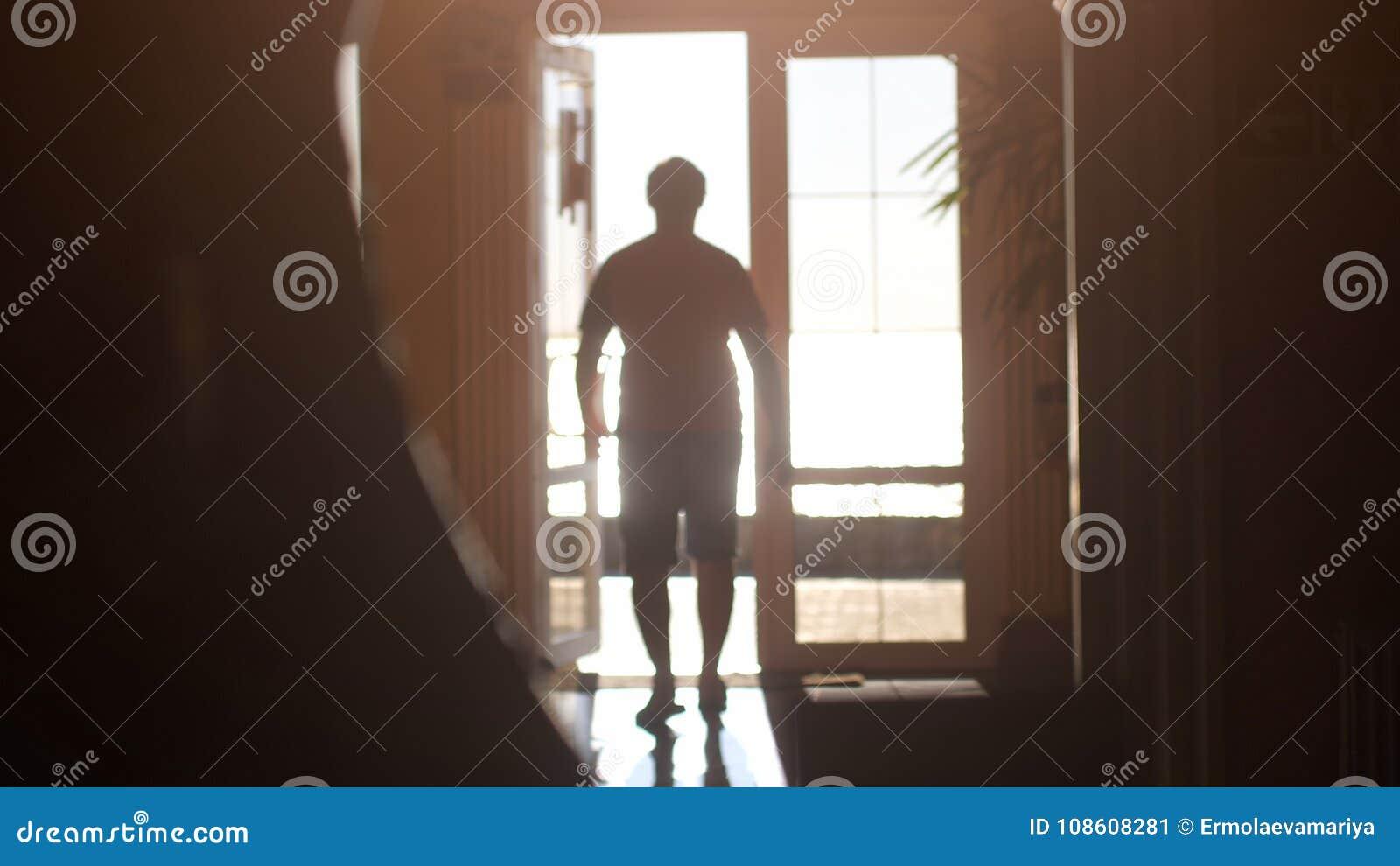Siluetta di un uomo che cammina verso l uscita lungo il corridoio alla luce solare durante il tempo di tramonto