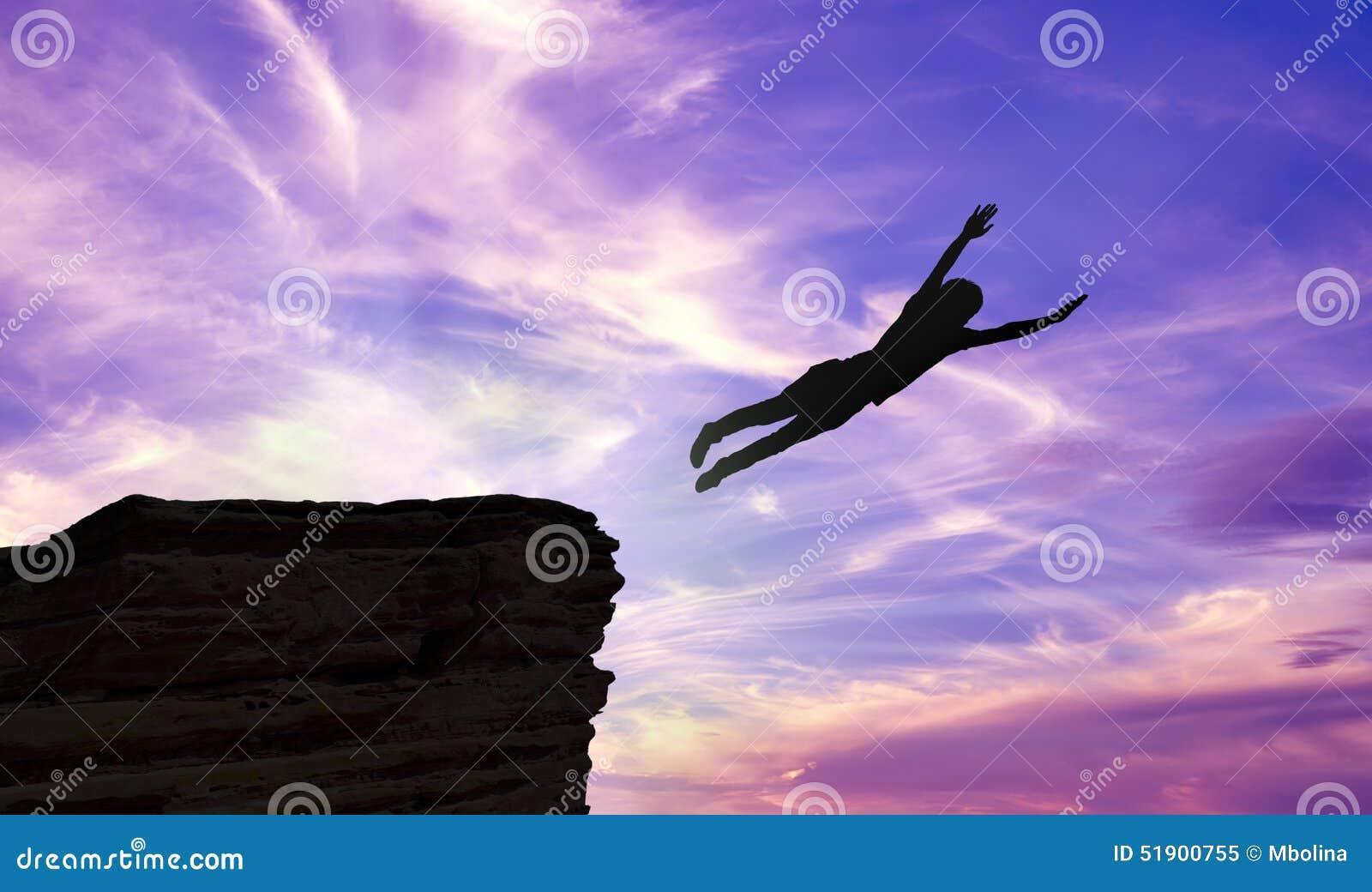 Siluetta di un uomo che salta giù una scogliera