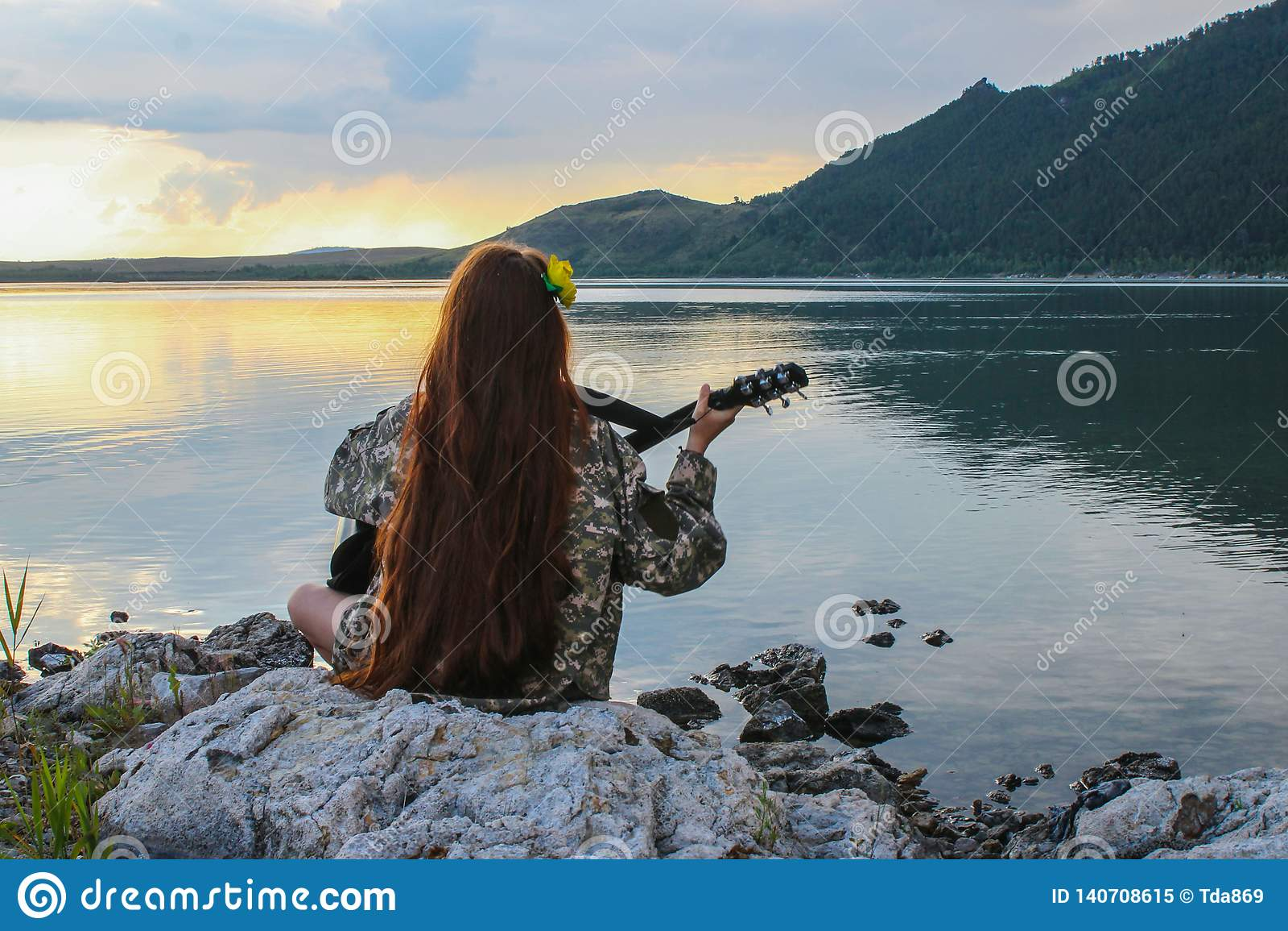 Siluetta di una ragazza al tramonto che gioca la chitarra dal fiume