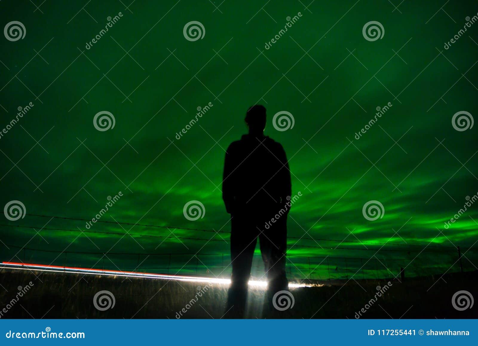 Siluetta epica dall uomo davanti all aurora boreale mentre a