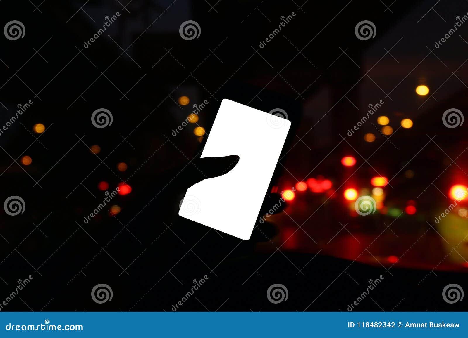 Siluetta nella notte dell automobile con la vista frontale dello Smart Phone moderno e dello schermo bianco in bianco vuoti per l