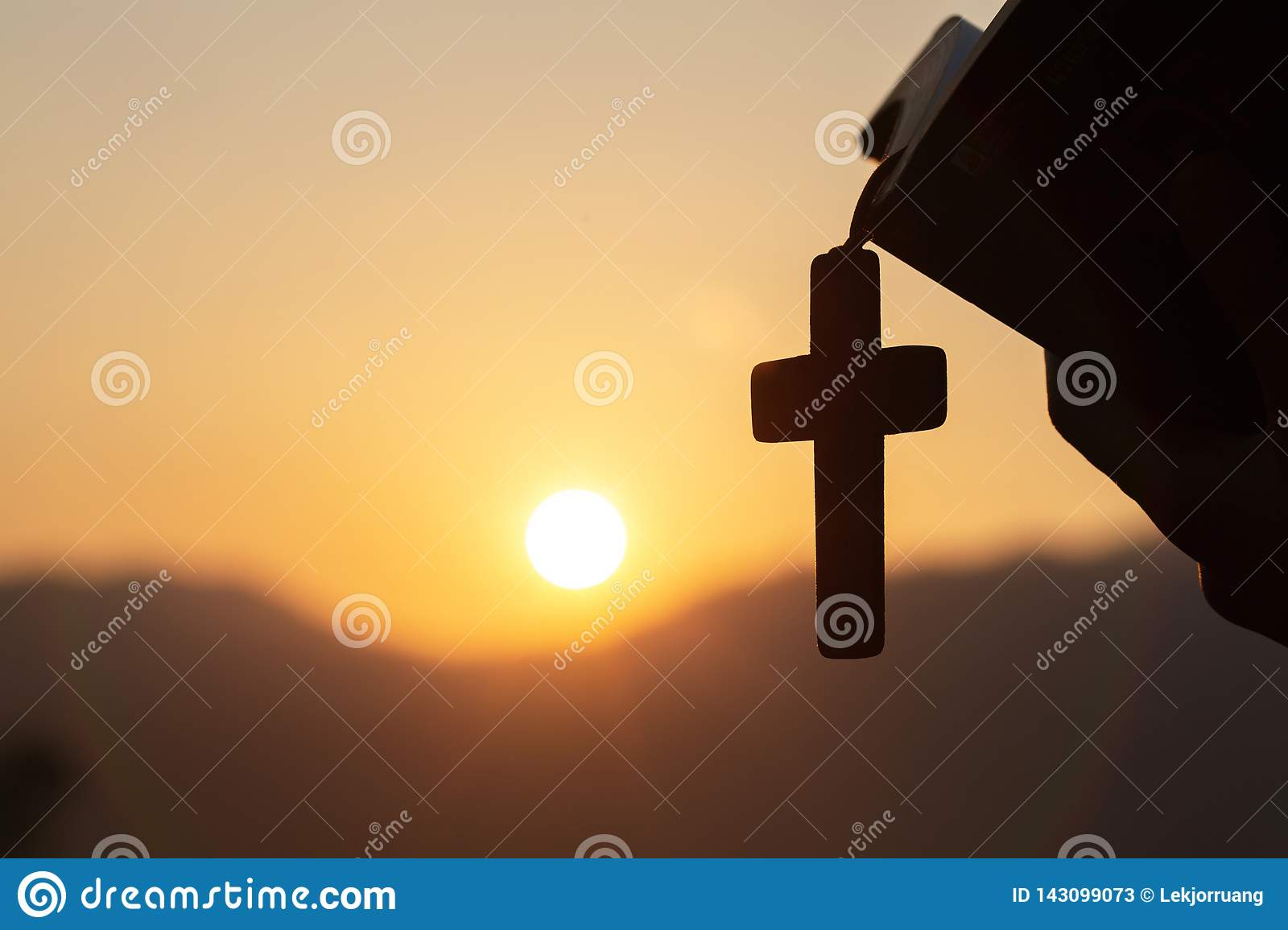 Siluette of Christian woman holding a bible and wooden Christian cross necklace while praying to God