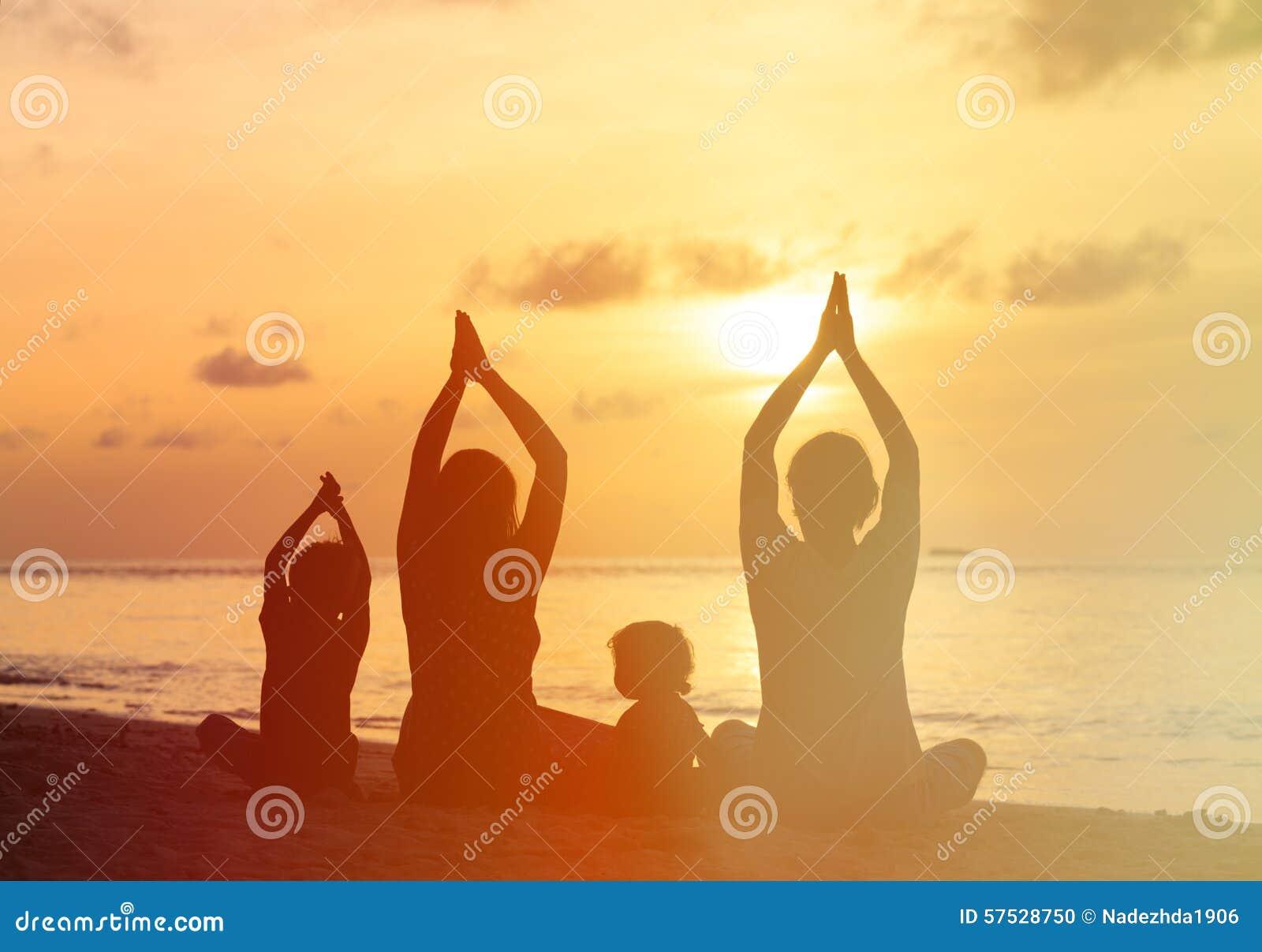 Siluette della famiglia che fanno yoga al tramonto