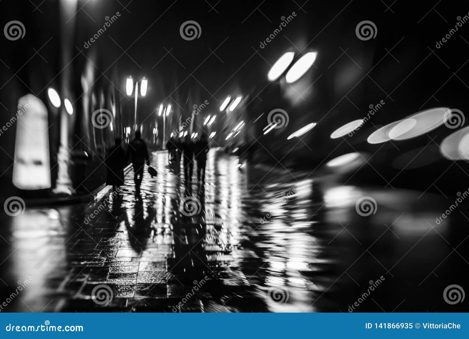 Siluette della gente come lo zombie che cammina alla notte nel piovoso alla luce delle lampade di via, fuoco vago molle