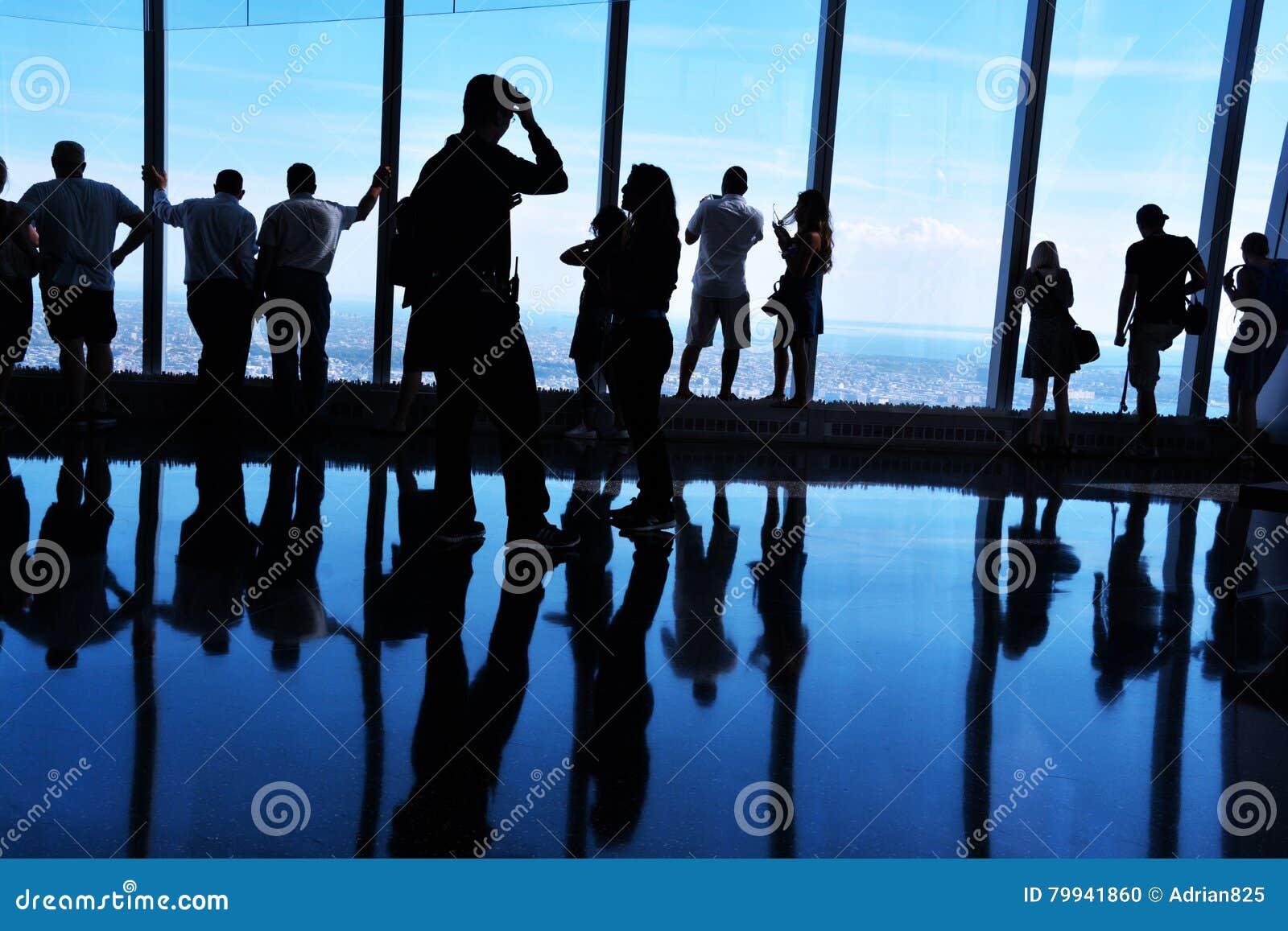 Siluette retroilluminate, la gente che esamina vista da un osservatorio del World Trade Center, Manhattan