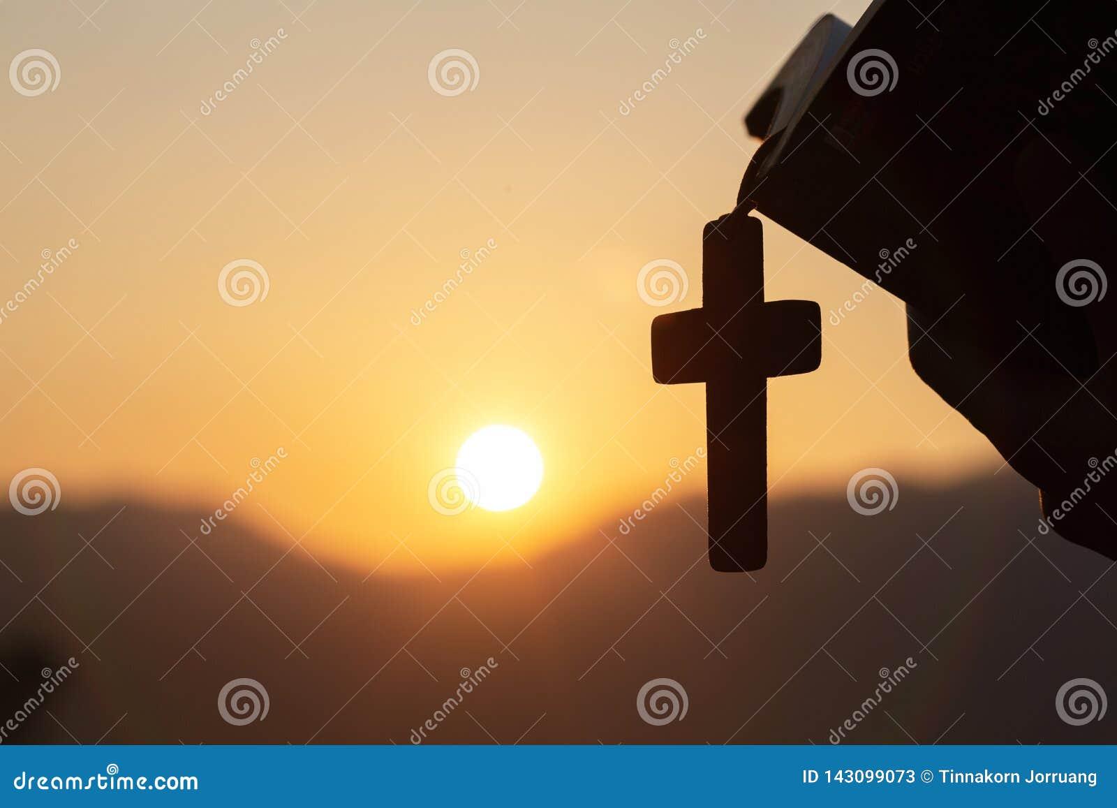 Siluette trzyma biblię Chrześcijańska kobieta i drewniany chrześcijanin krzyżujemy kolię podczas gdy ono modli się bóg