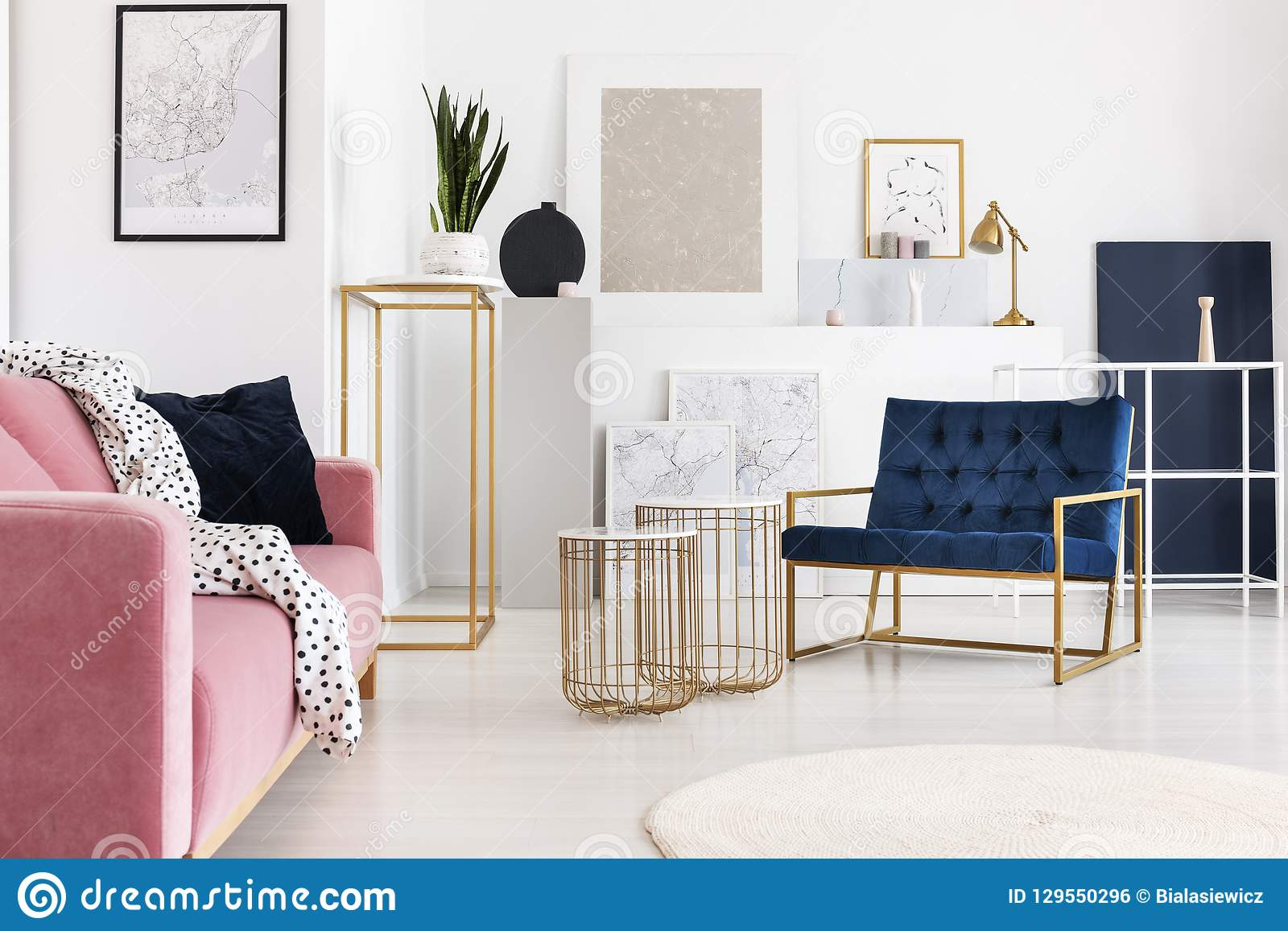 Silver painting on the wall of trendy living room with two elegant coffee tables, petrol blue armchair and powder pink