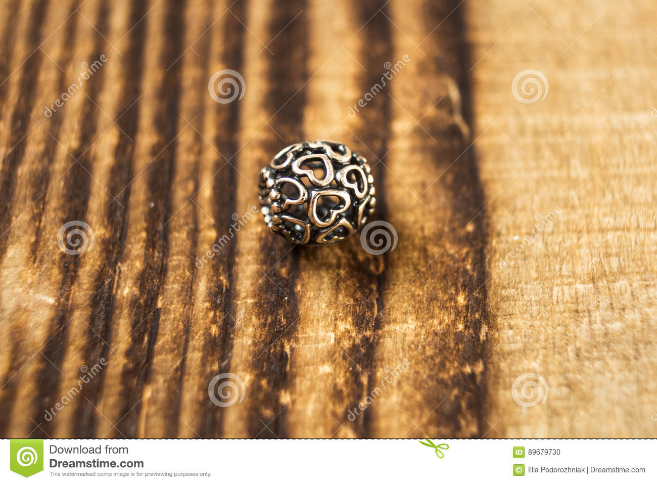 Silver bead for bracelet on wooden background