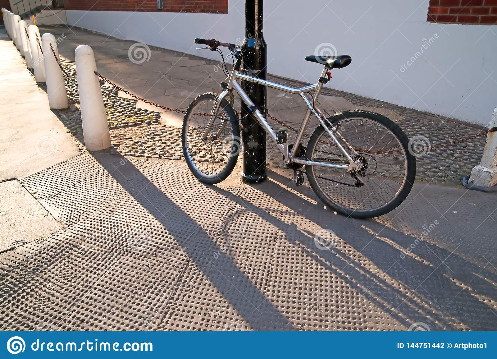 Silver bicycle chained to a lamppost