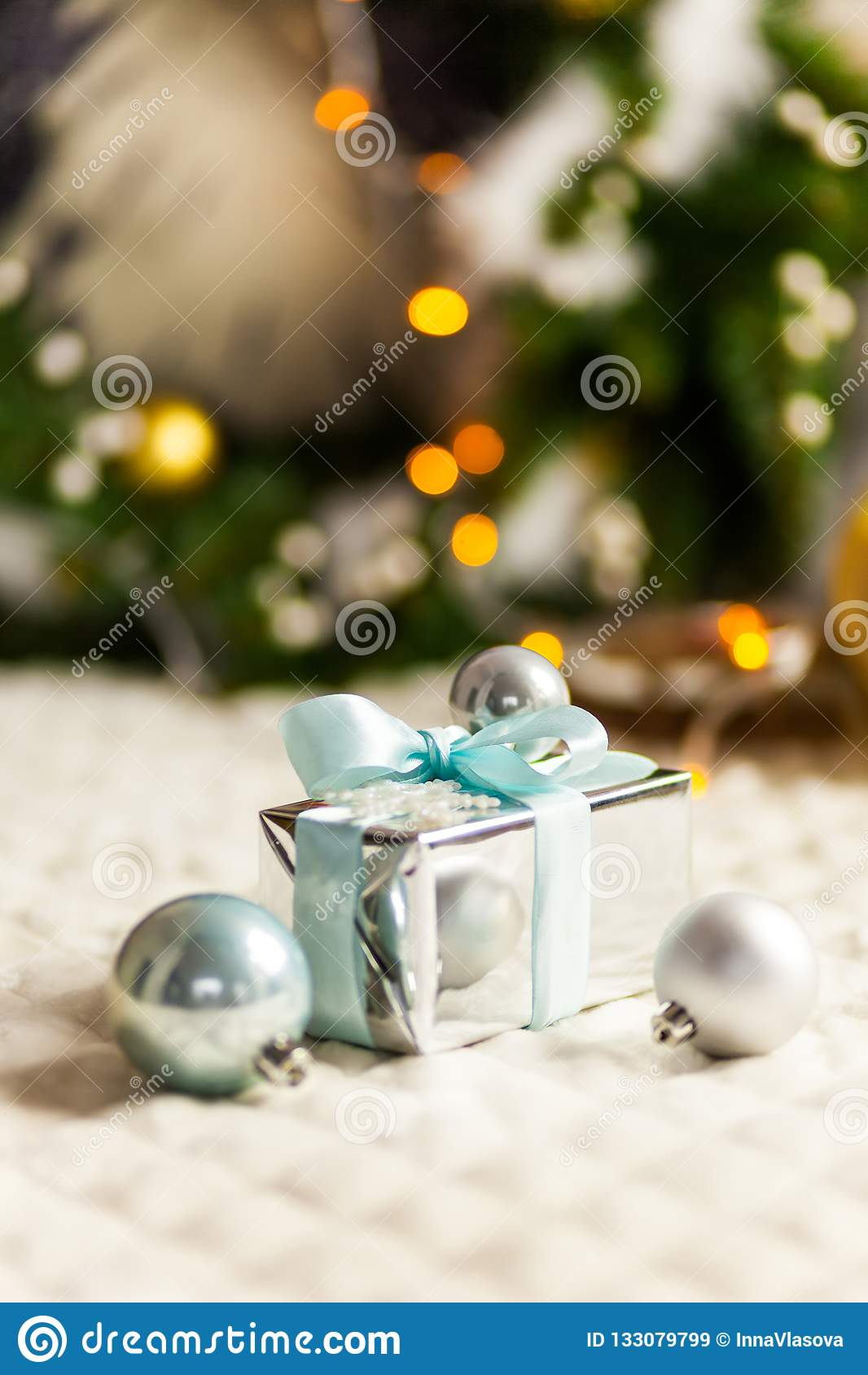 The Silver and blue Christmas balls and gifts on festive lighting background
