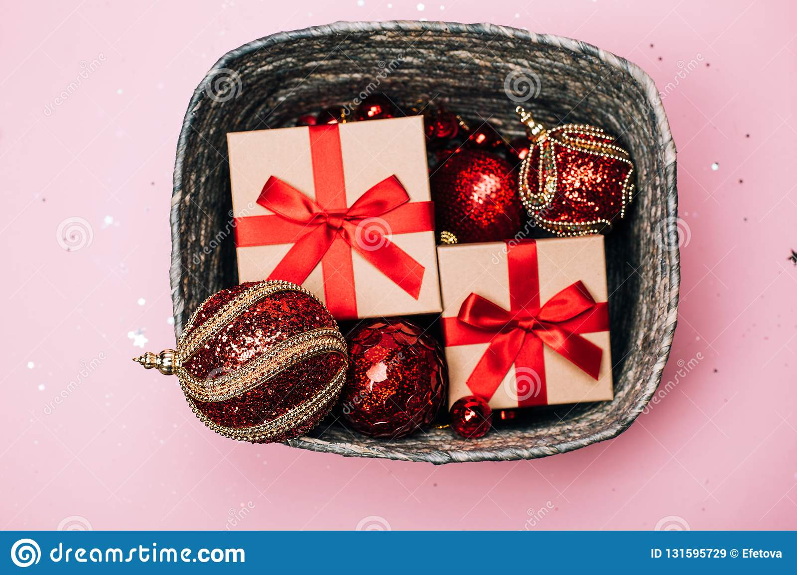 Silver box with presents and red christmas balls on pink pastel background.