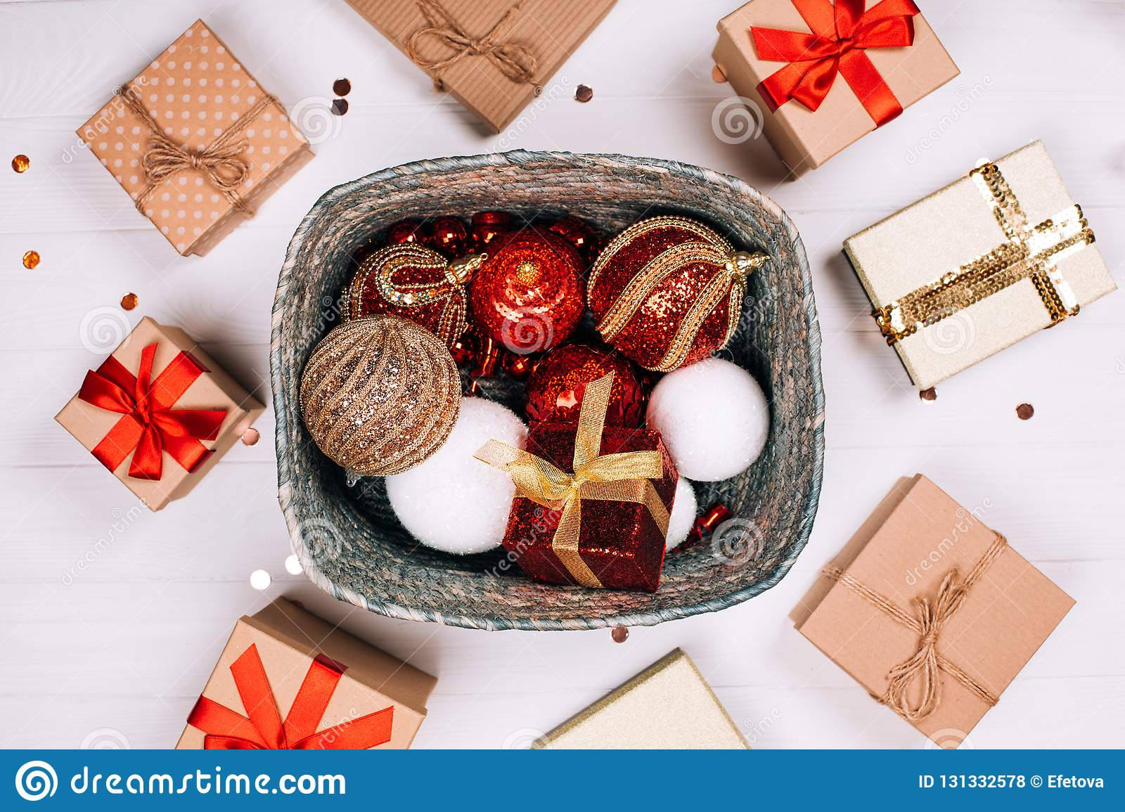 Silver box of red balls with round of presents on white wooden background.