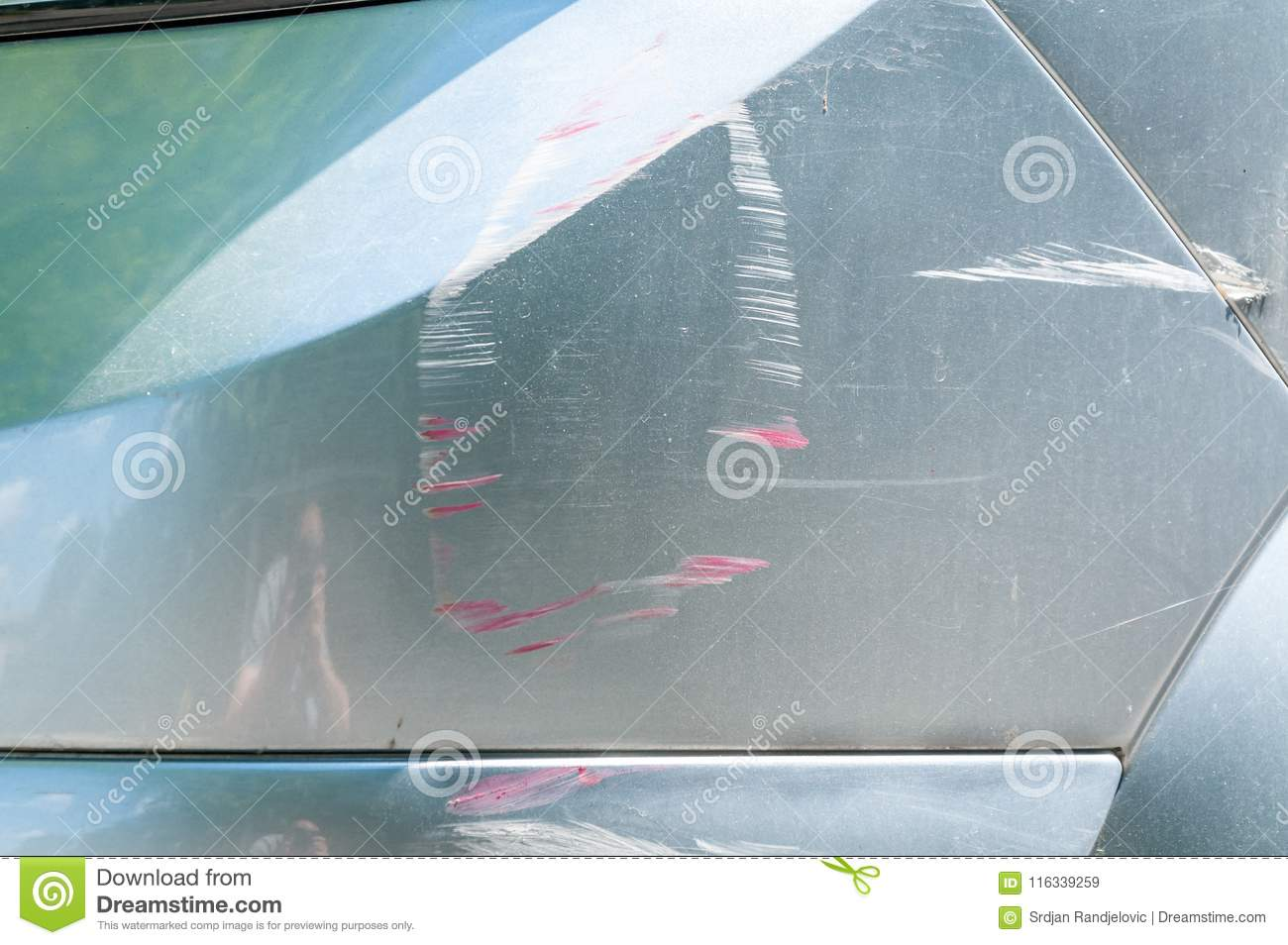 Silver car with scratched paint with red lines of other vehicle damaged in crash accident or parking lot, close up