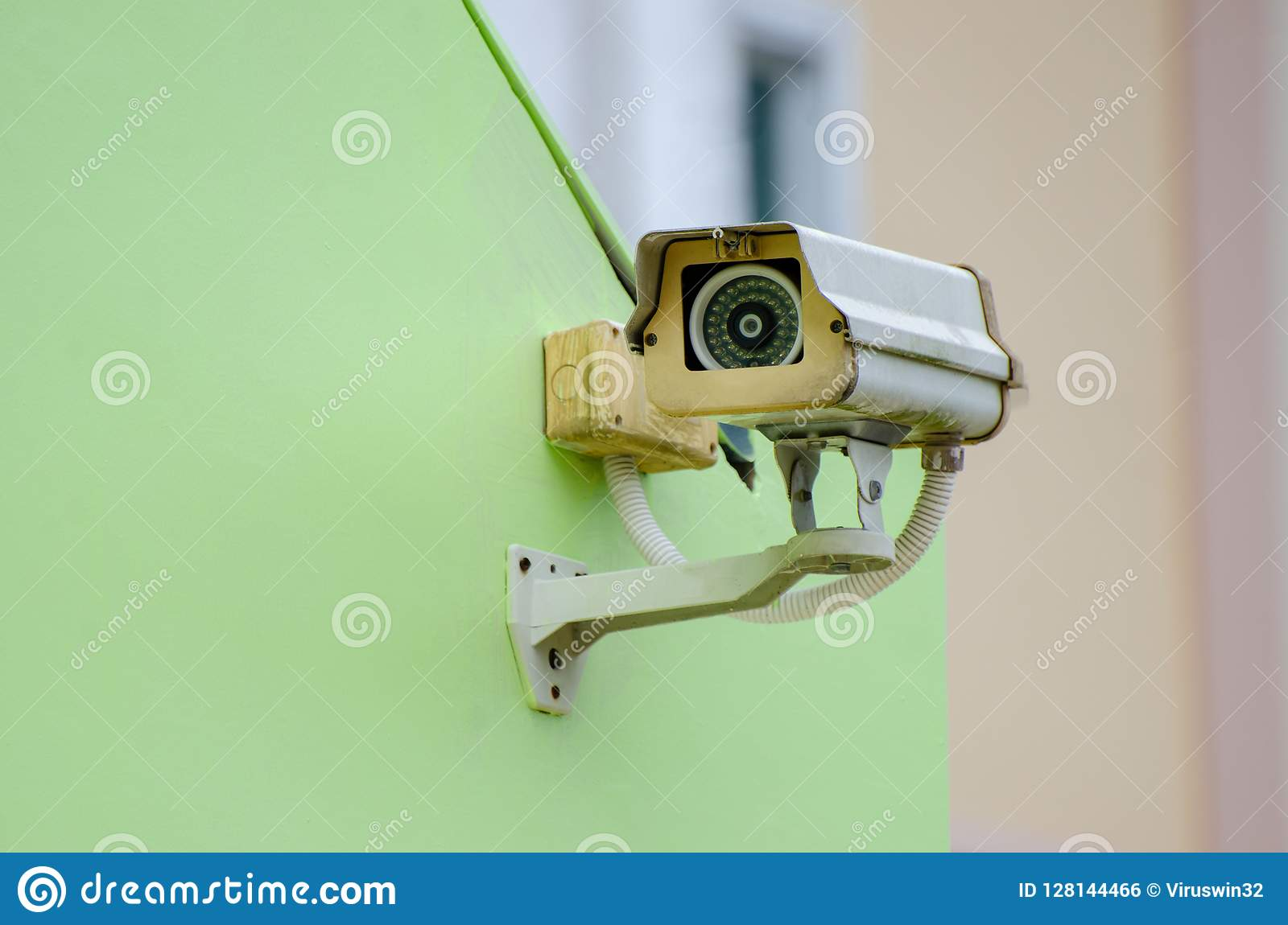 Silver CCTV Camera on the green wall Closed Circuit Television camera on green background