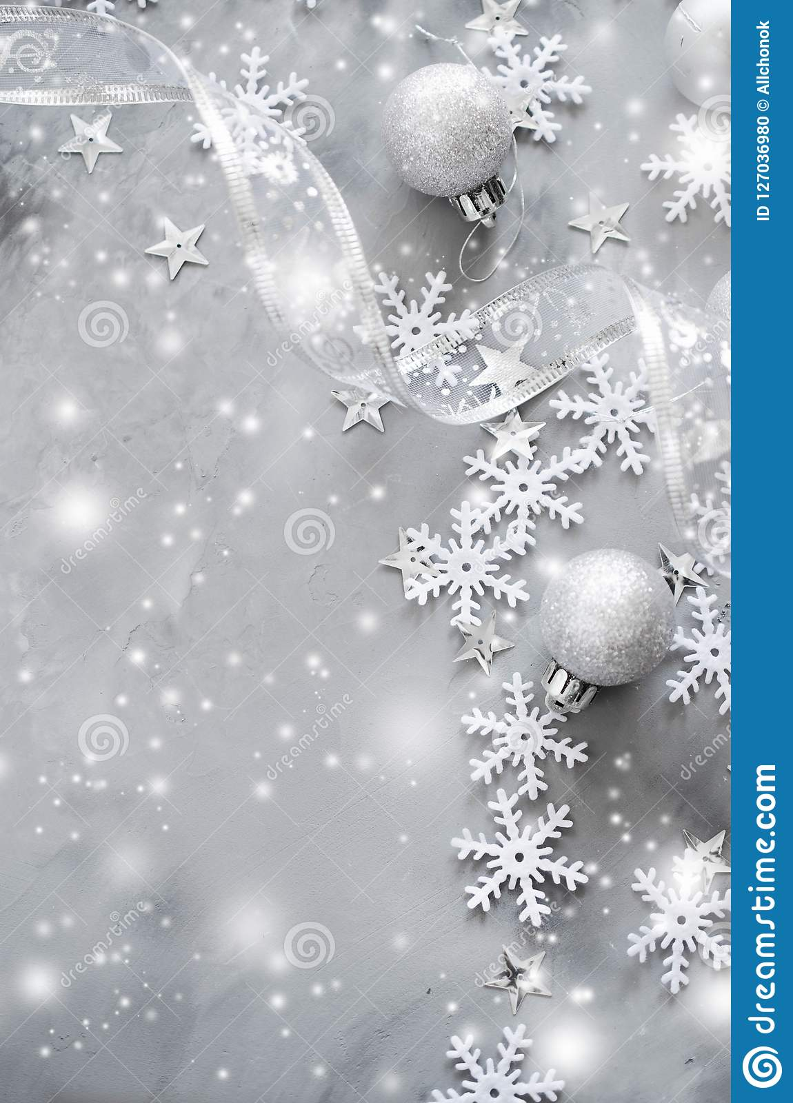 Silver Christmas background. Curly ribbon with decorative balls and snowflakes.