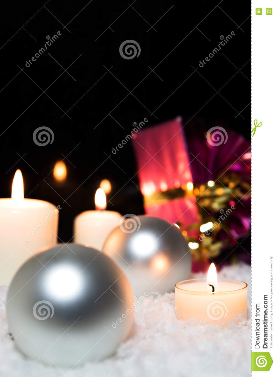 Silver christmas balls, candles and a red gift in the snow